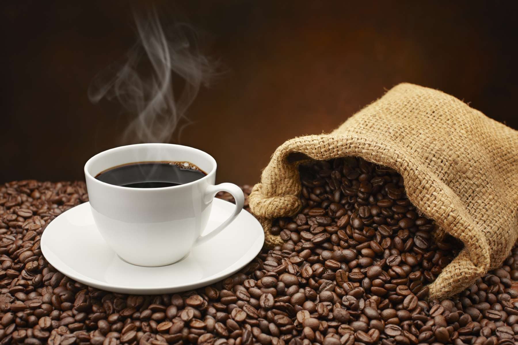 m Steaming-cup-of-coffee-on-pile-of-coffee-beans-000019447735_Large ...