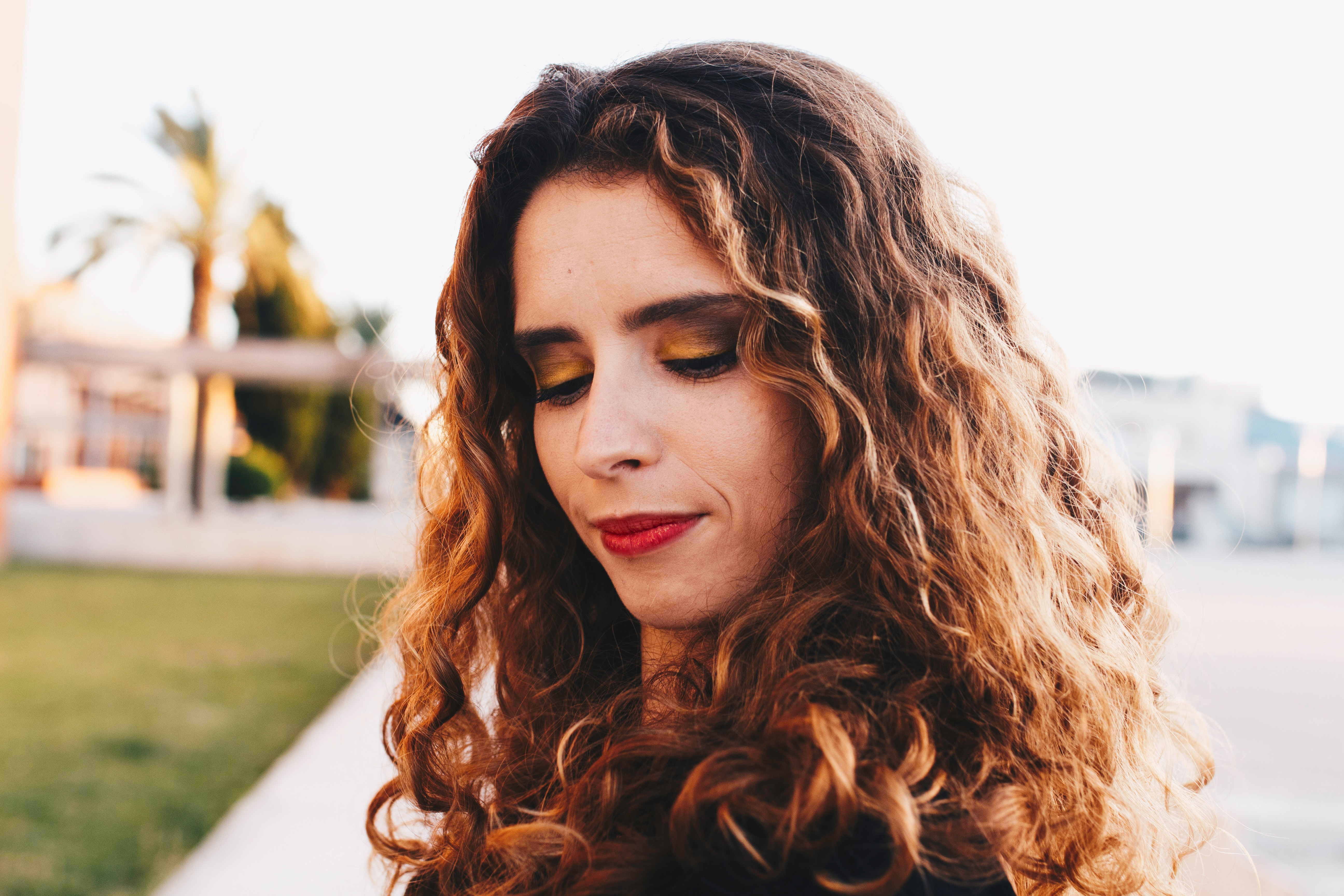 Curly Brown Haired Woman Wearing Black Shirt With Red Lipstick Looking Down, Blurred background, Outdoors, Woman, Wear, HQ Photo