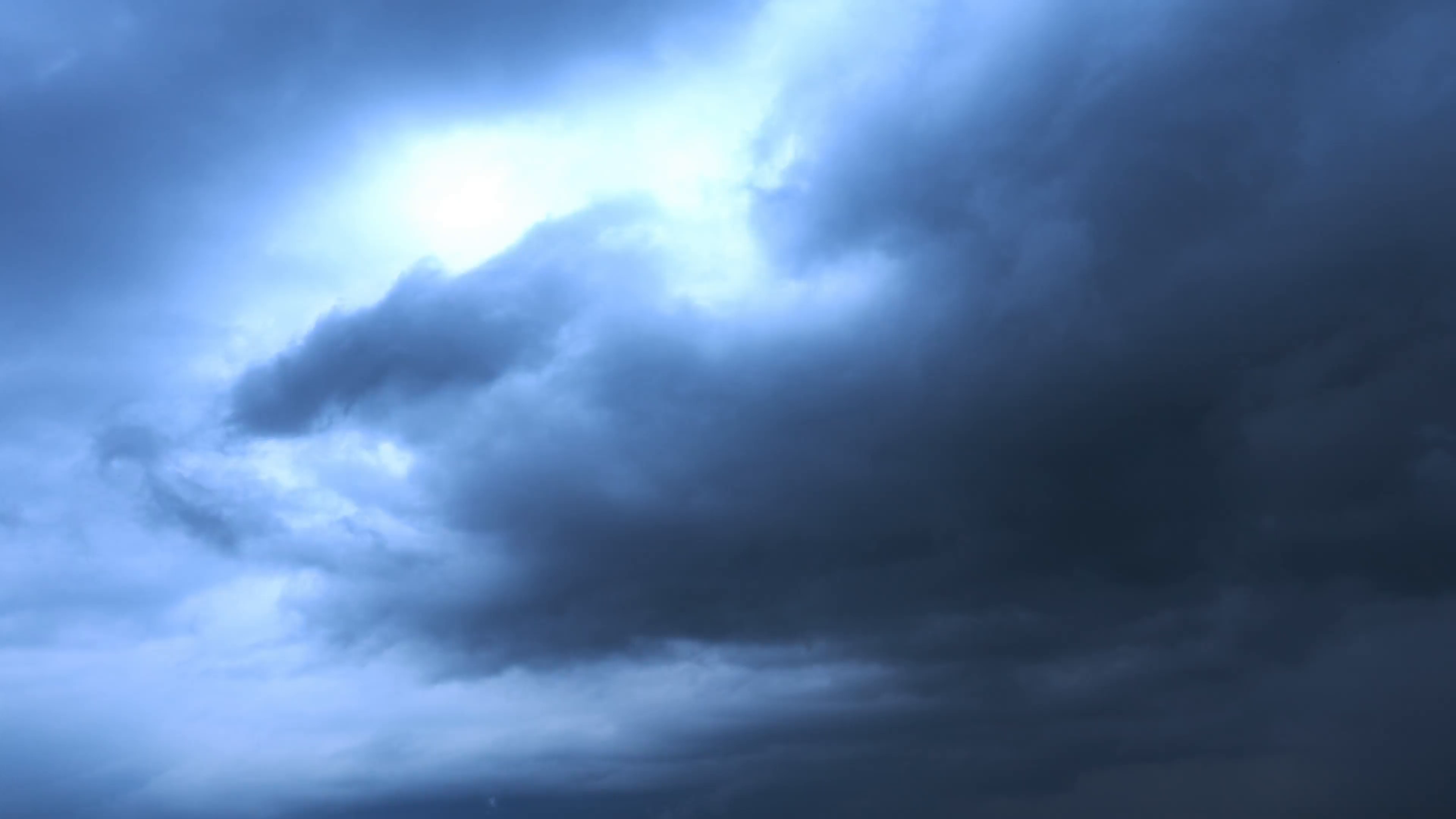 Dramatic dark blue storm clouds with bright light 4K extreme nature ...