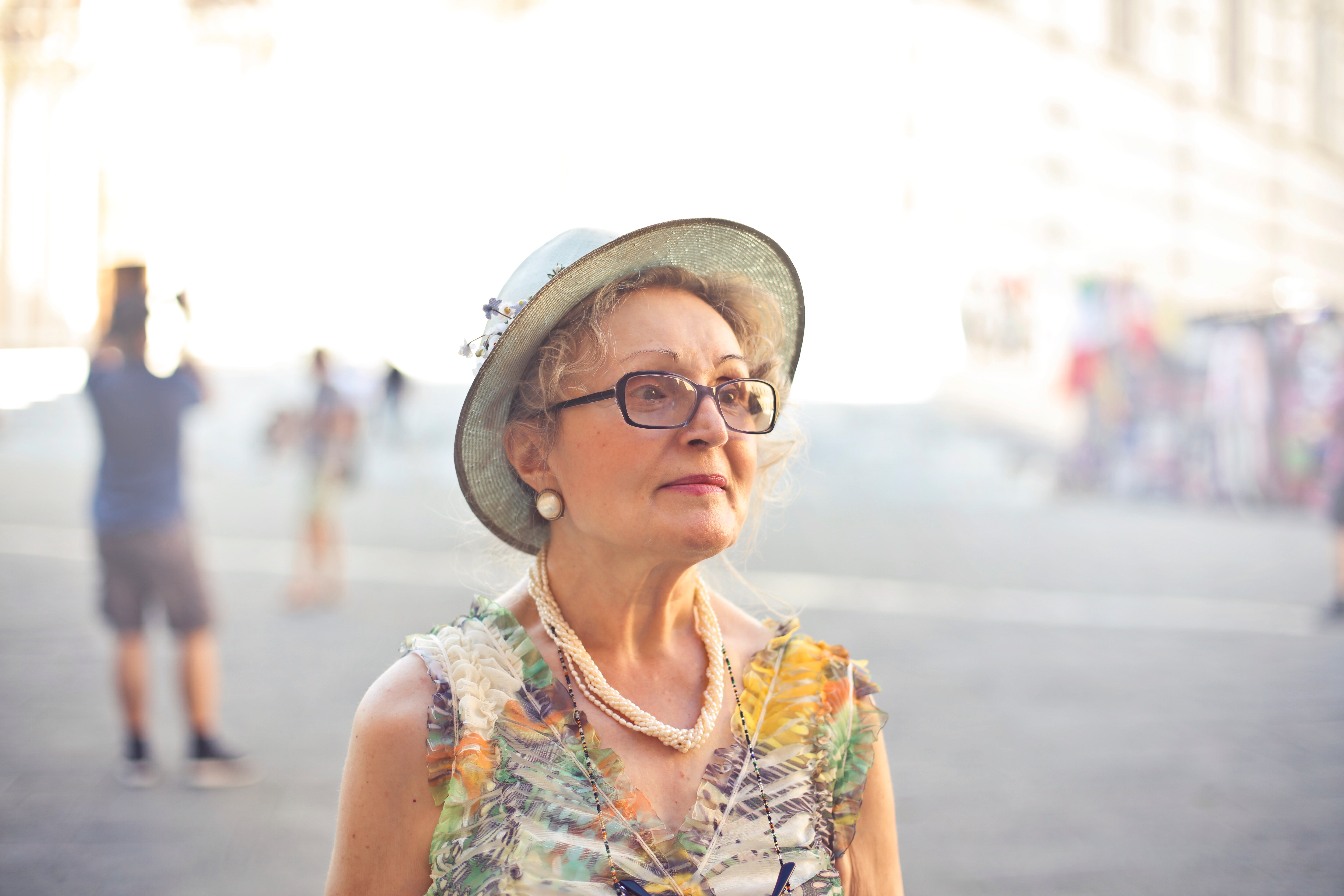 Depth of field photography of woman in pastel color sleeveless shirt and white sunhat