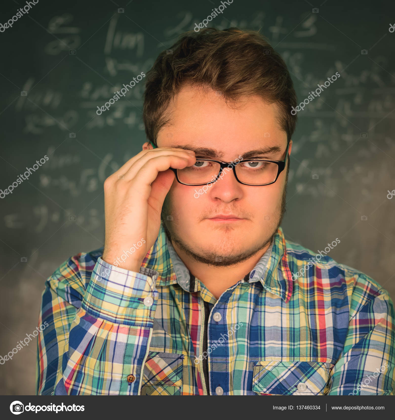 Full man in glasses close-up on a background blackboard with ...