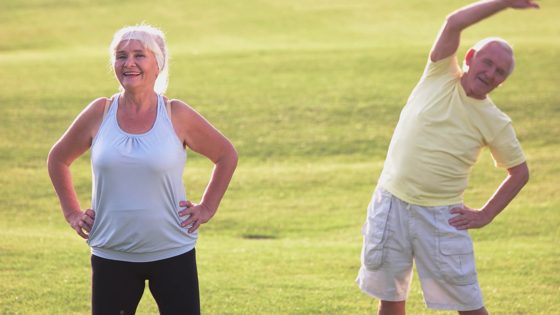 Elderly couple doing exercise. Man with woman on meadow. Gymnastics ...