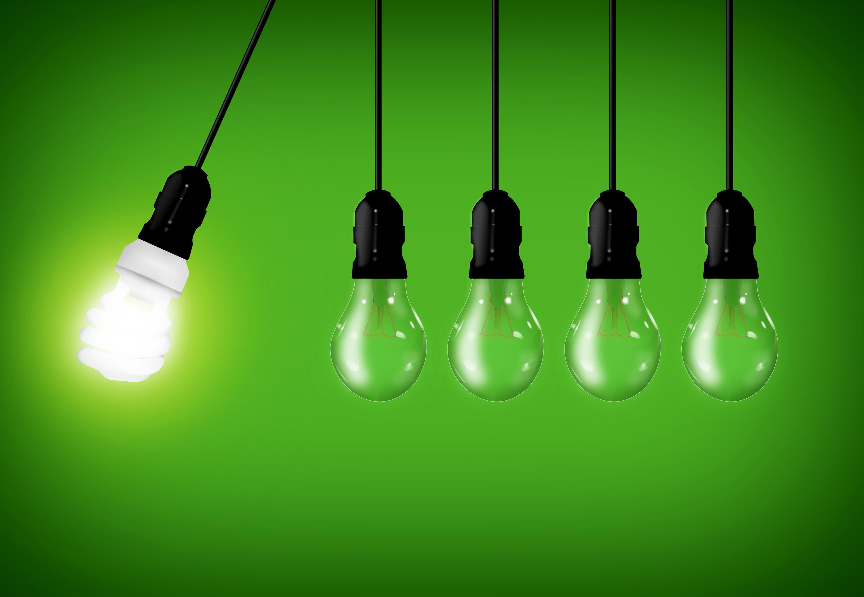 Eco concept - energy saver lightbulb among common lightbulbs photo