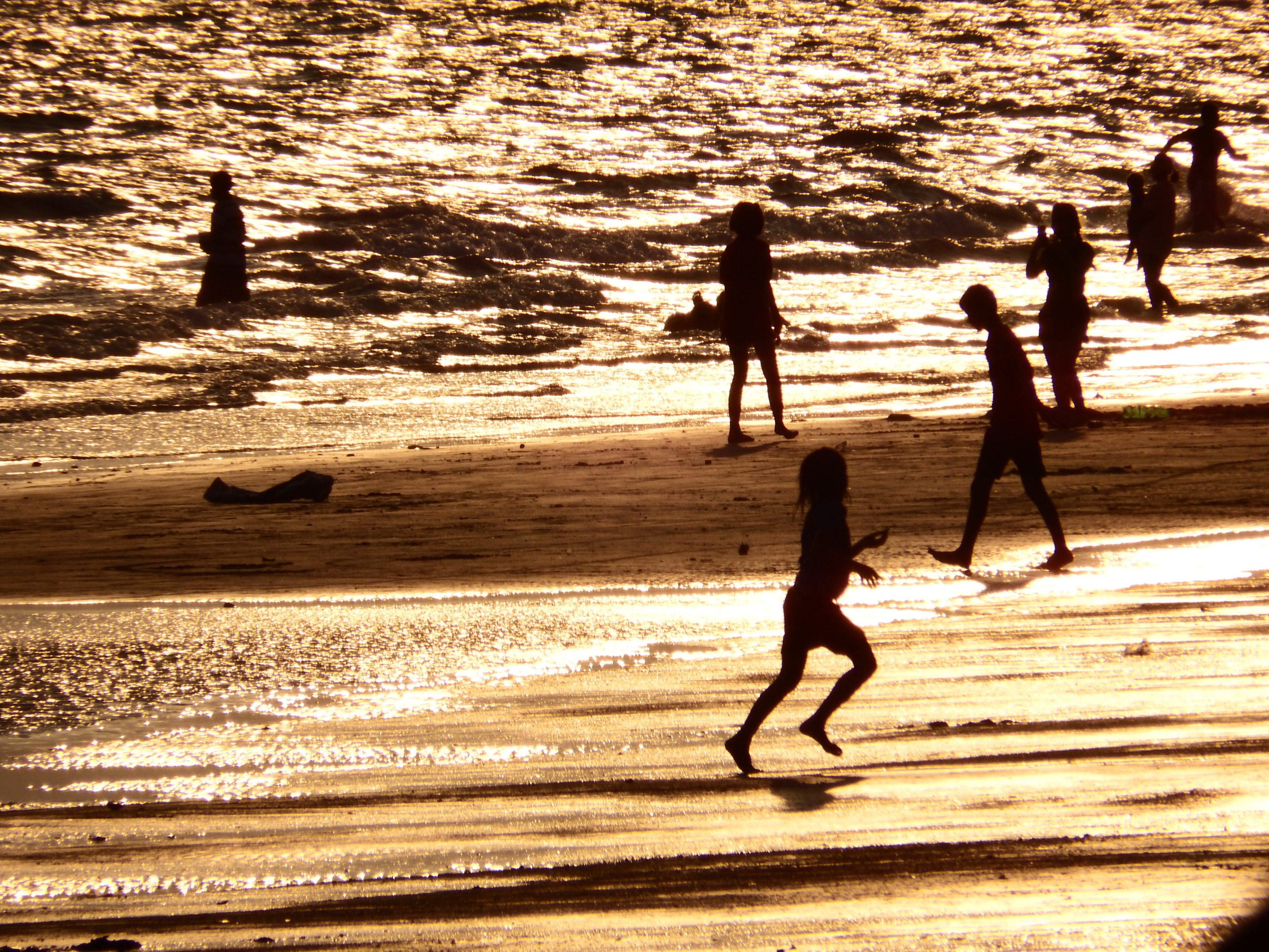Family plays on the beach silhouette photo
