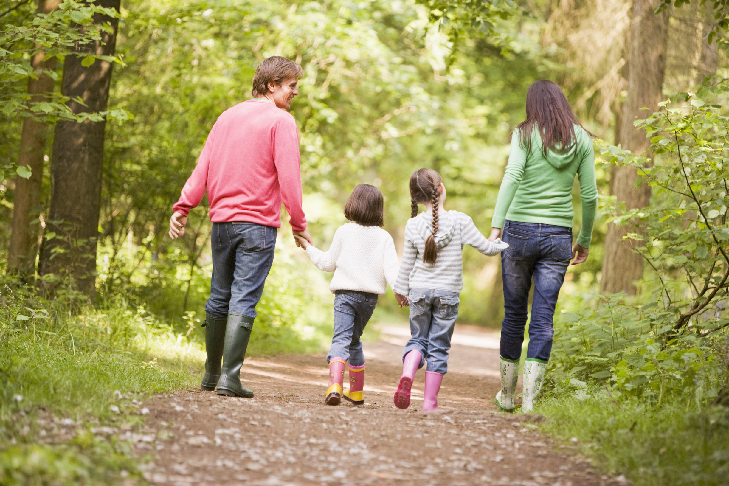 Family walking on path holding hands - The OrganWise Guys