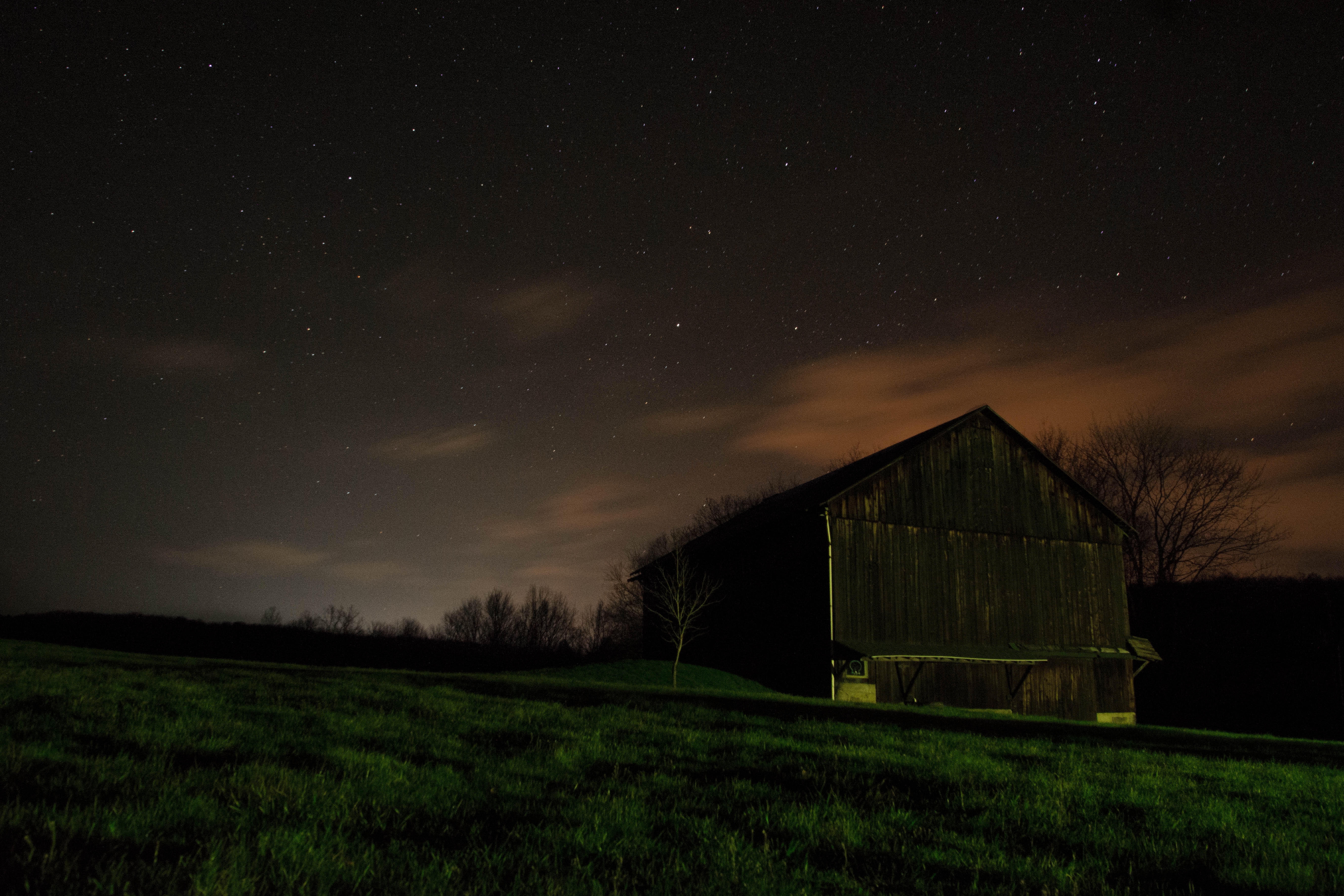 Farm house at night under sky filled with stars photo