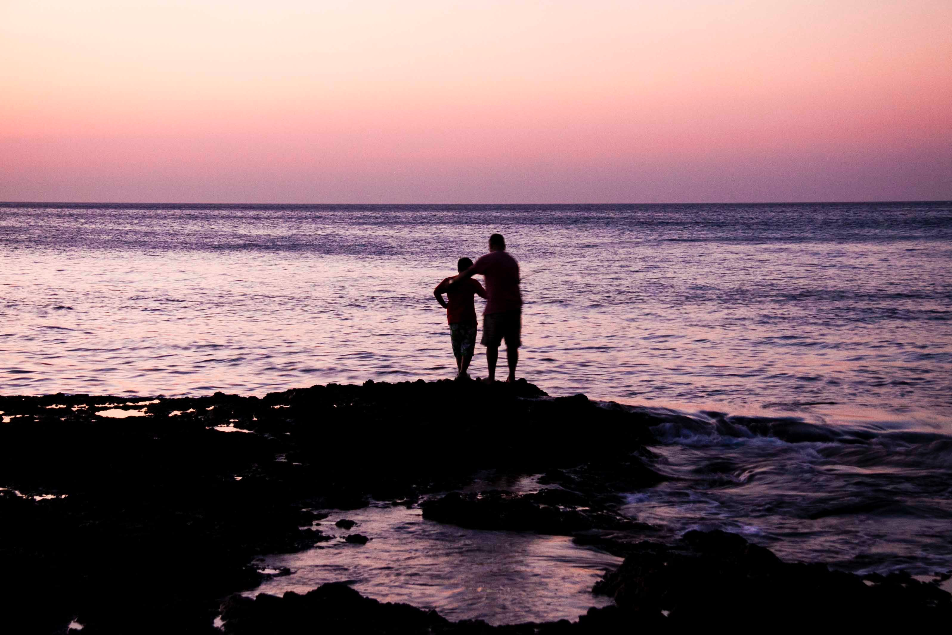 Father and child near on body of water during sunset photo
