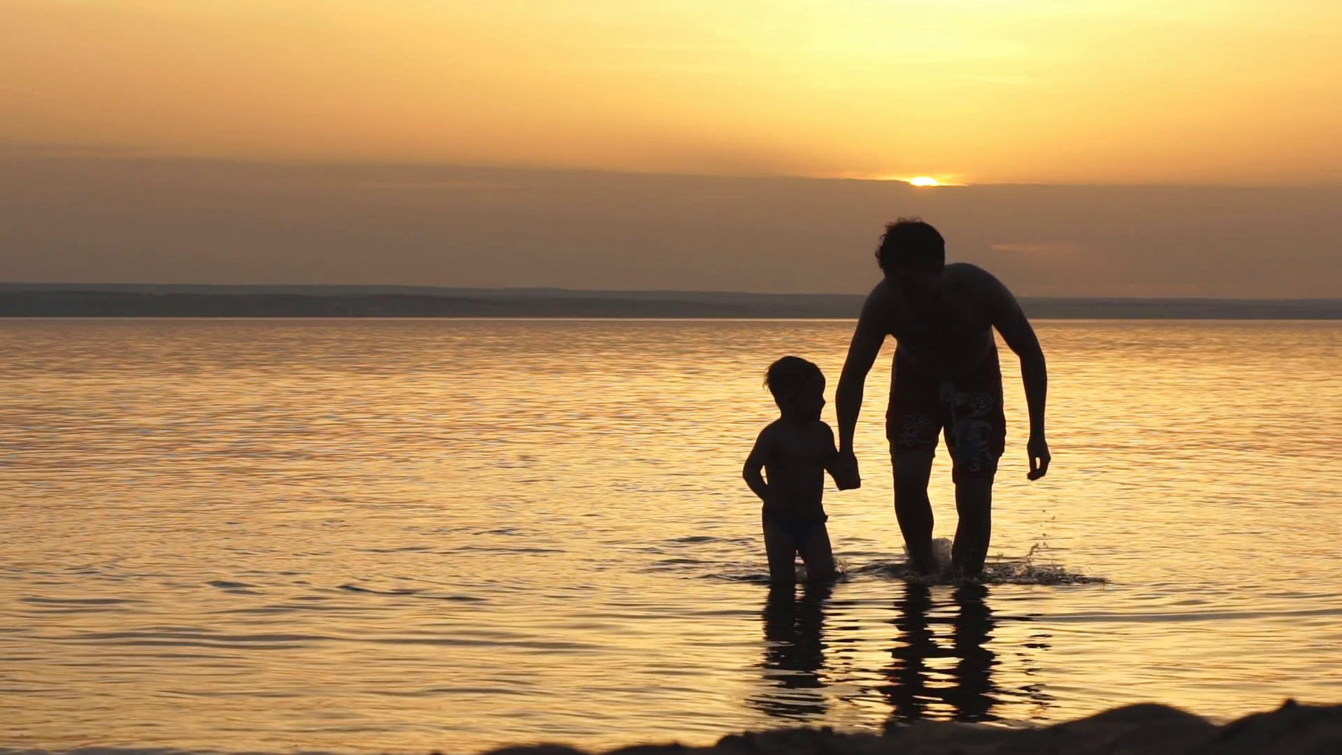 Father and Son Holding Hands Walking Together on the Beach at Sunset ...