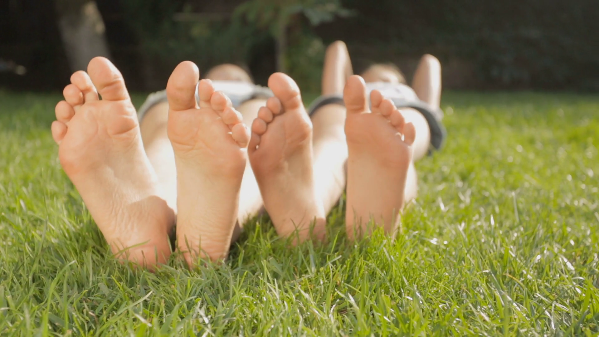 Dolly shot of two girls feet relaxing on grass at sunny day Stock ...
