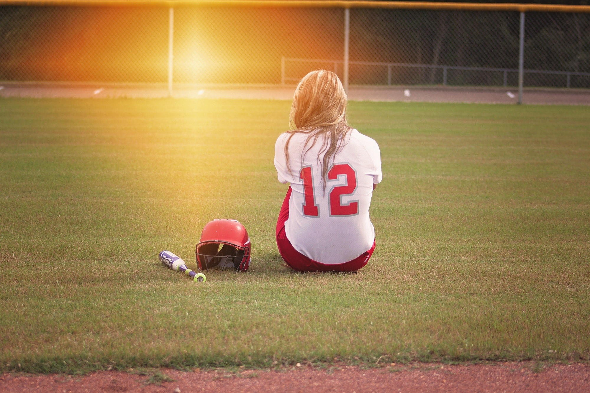 Female baseball player sitting on grass field beside helmet and baseball bat photo