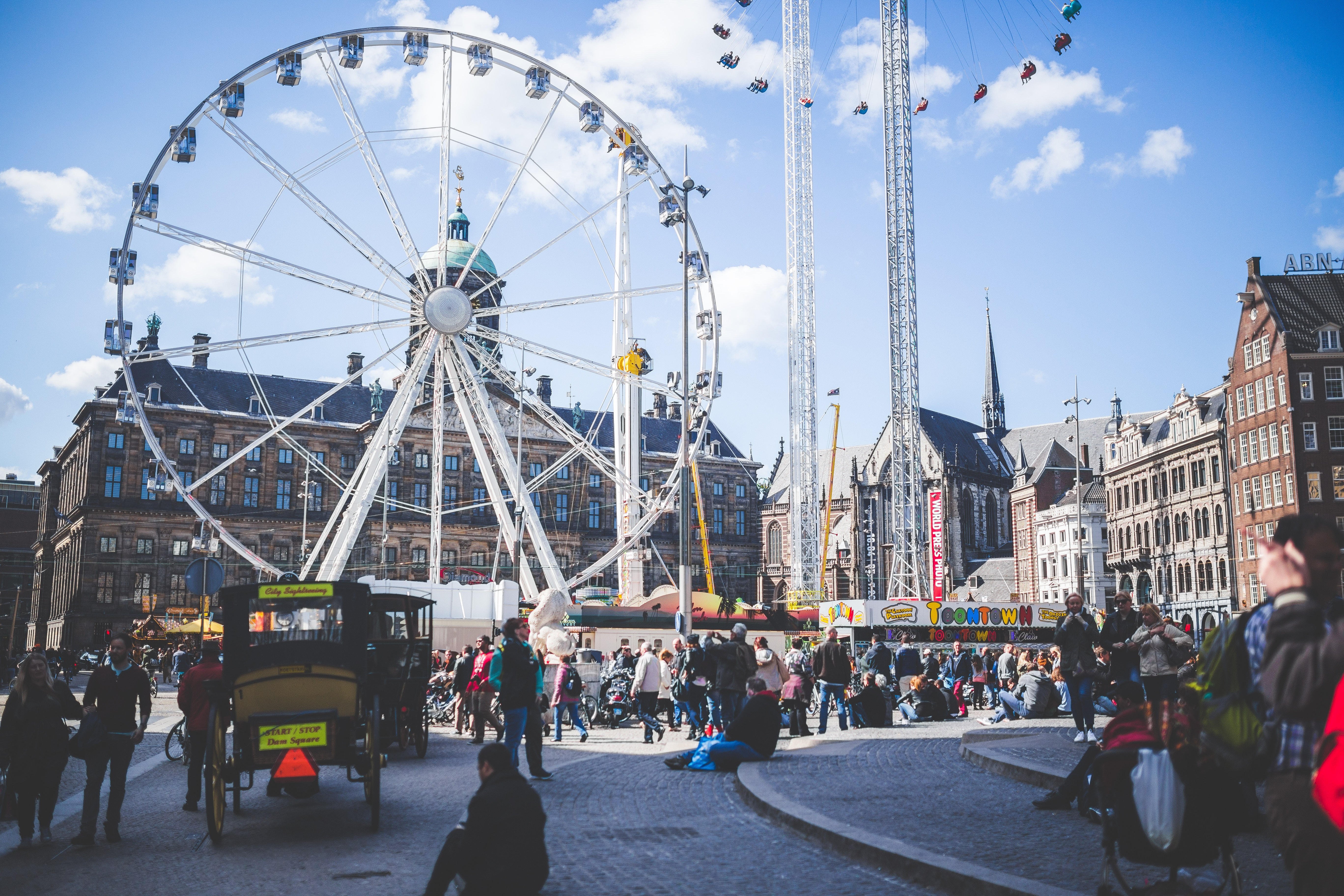 Ferris wheel beside brown buildings and people under blue cloudy sky at daytime photo