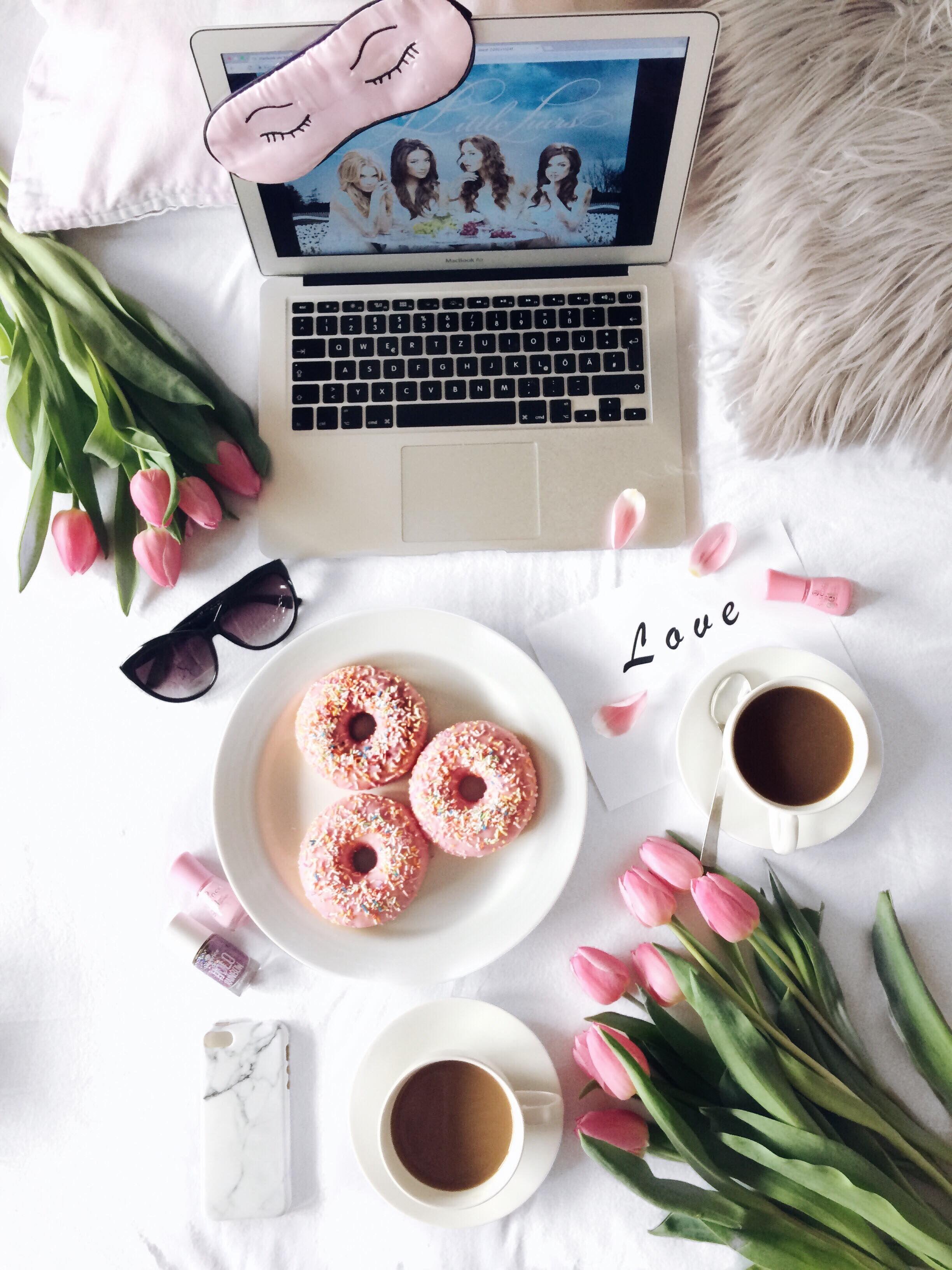 Süßes Flatlay mit Mac Book, pinken Donots, pinken Tulpen, Kaffee ...