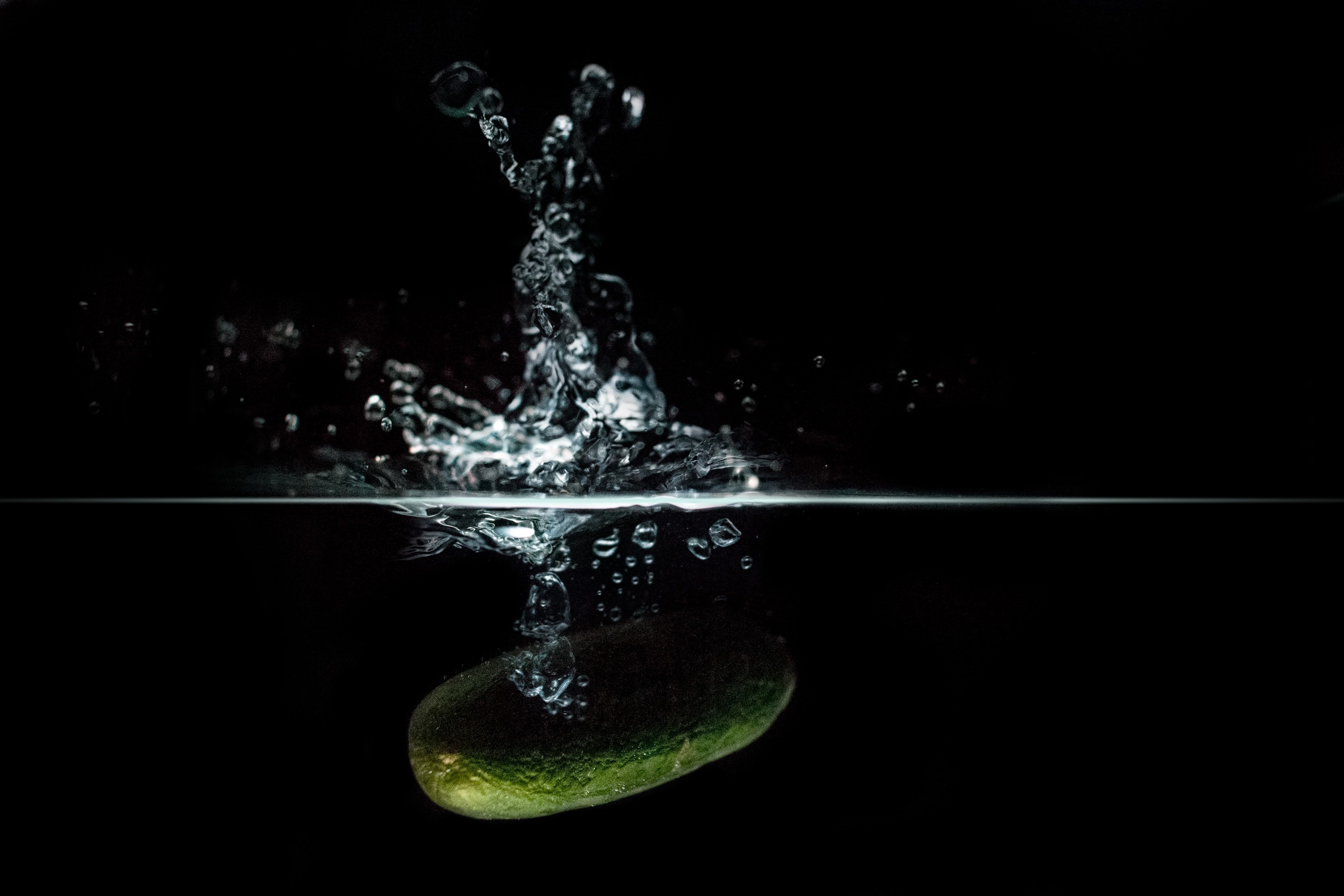 Focus photo of green vegetable dropped on water