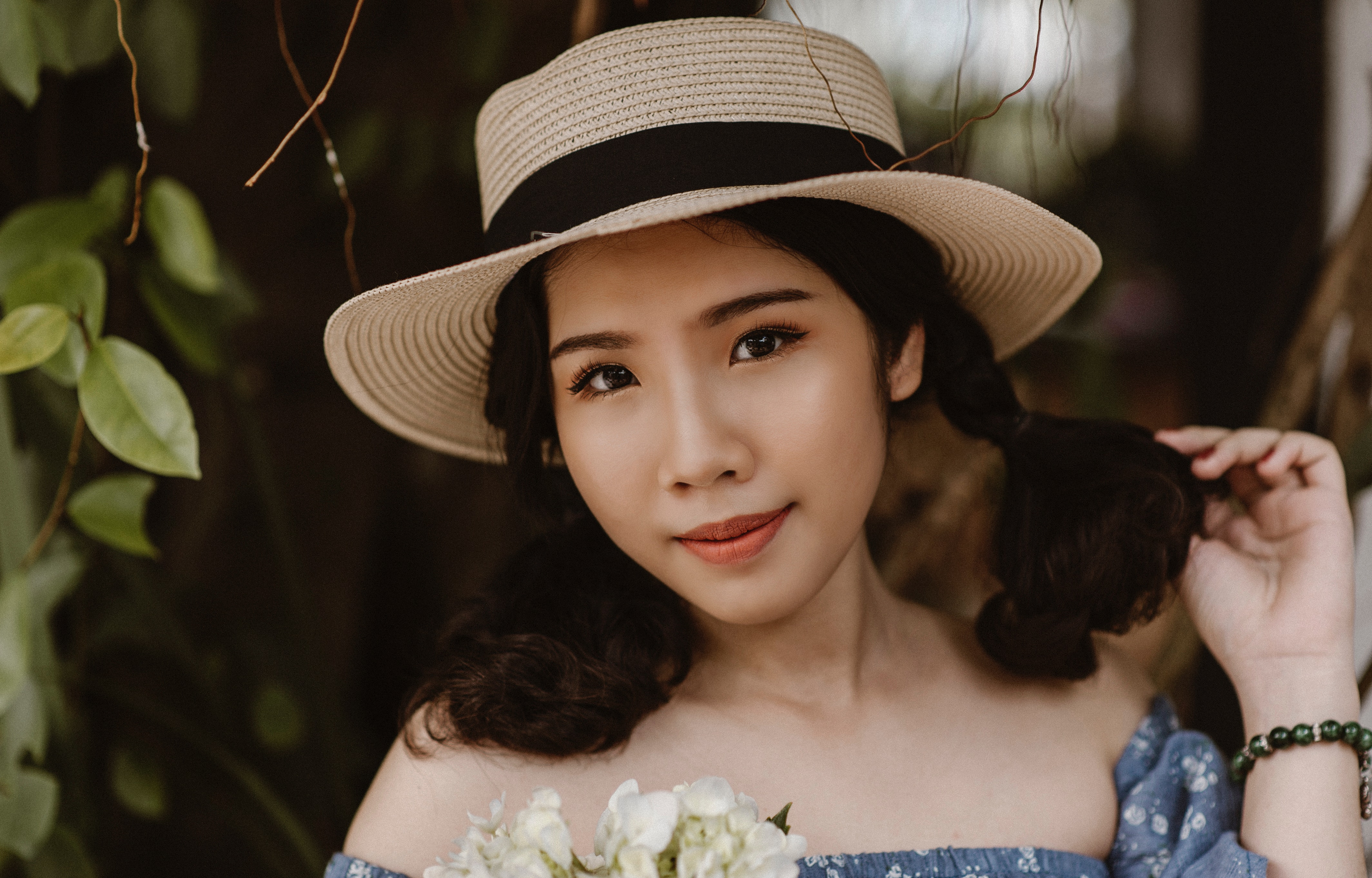 Focus photography of woman in brown sunhat near vine plant