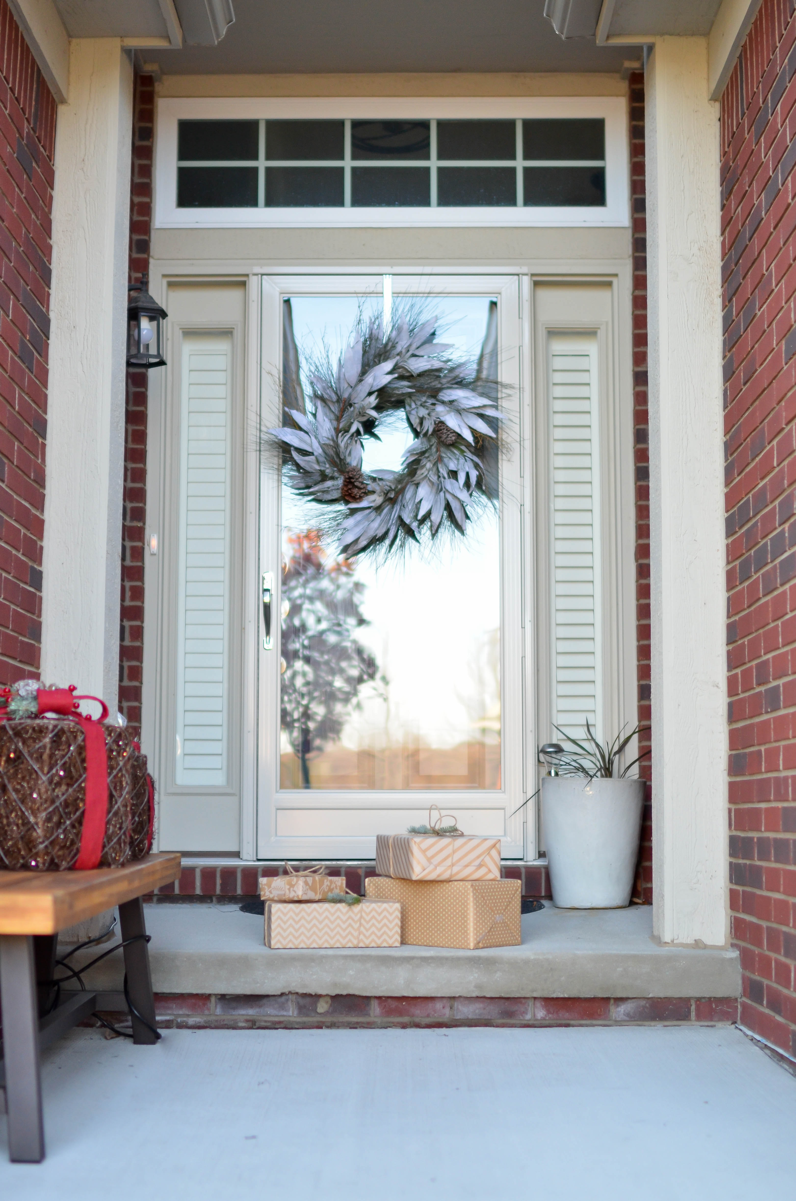 Four brown gift boxes near a glass paneled door with wreath photo