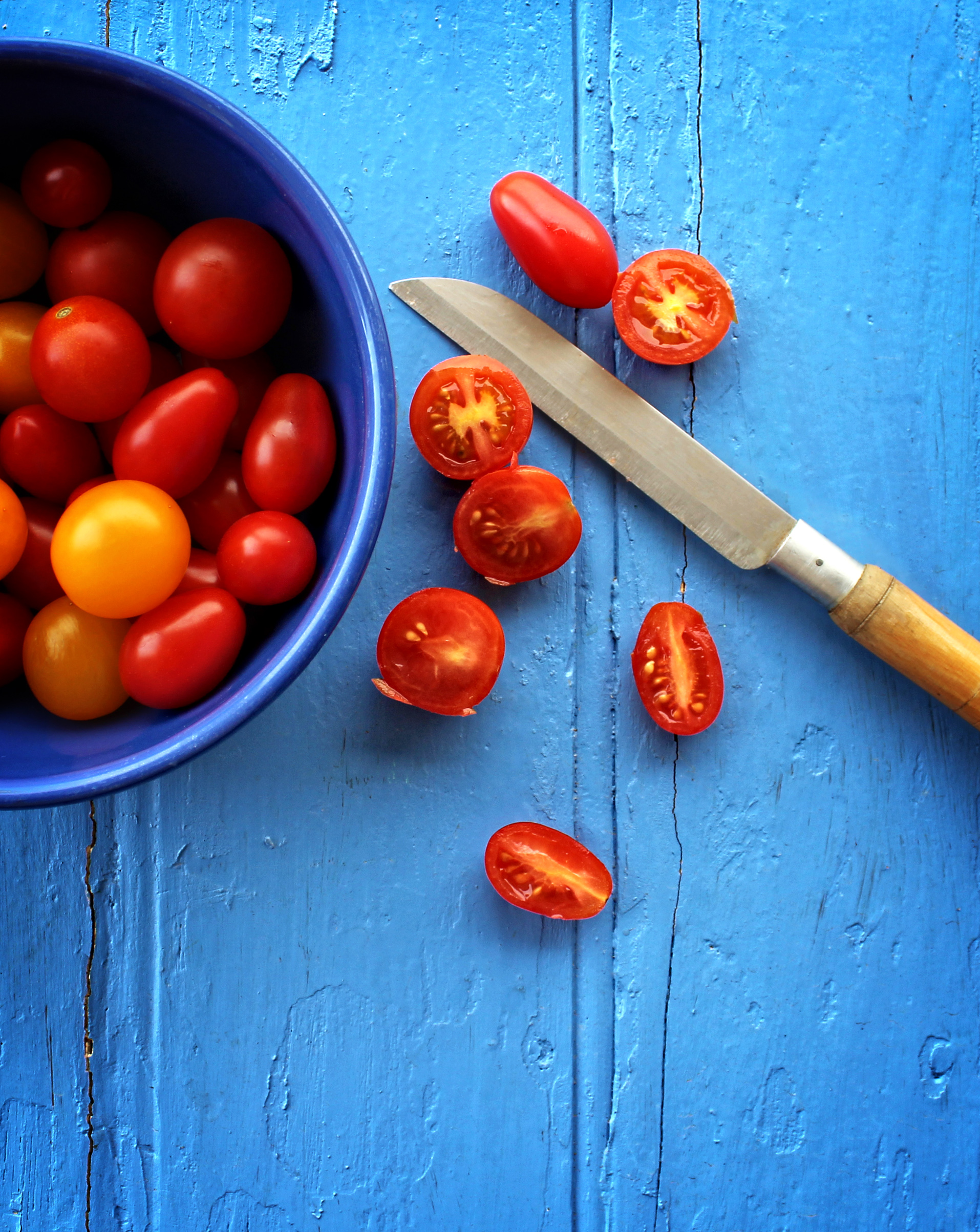 Freshly sliced organic cherry tomatoes on blue wooden background photo