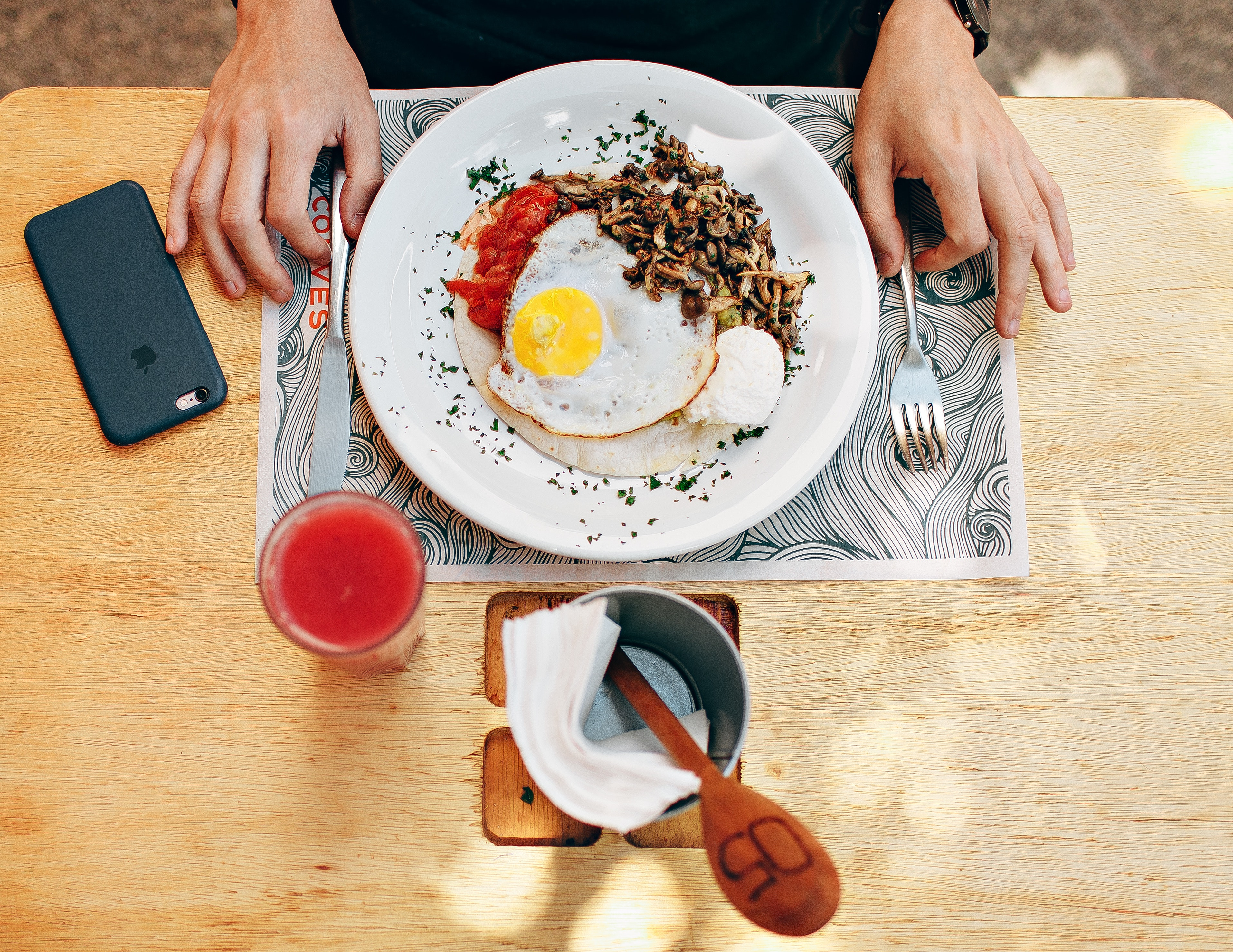 Fried egg with plain rice on white plate beside stainless steel fork with clear drinking glass on top table photo
