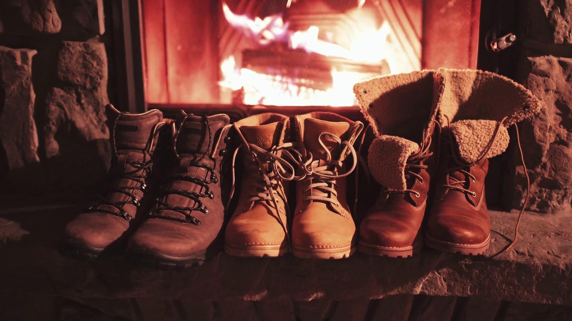 Woman Hand takes Warm Winter Boots from a Shelf near Fireplace. 4K ...