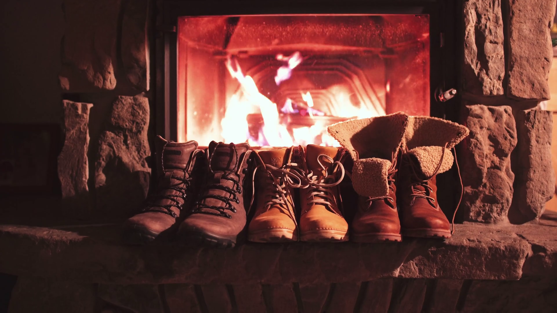 Winter boots in front of a fireplace 4K. Family vintage folk boots ...