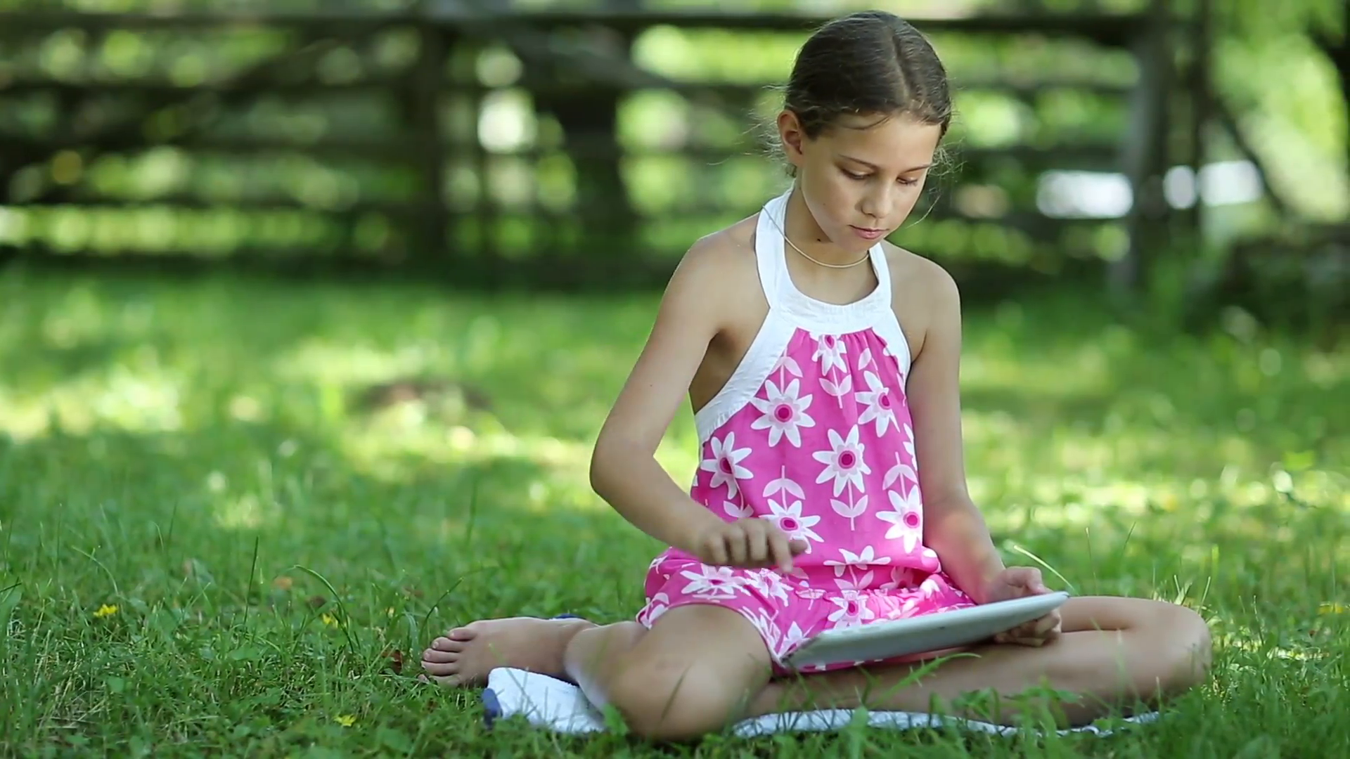 Little girl with Tablet-PC sits on the grass in the garden. Pretty ...