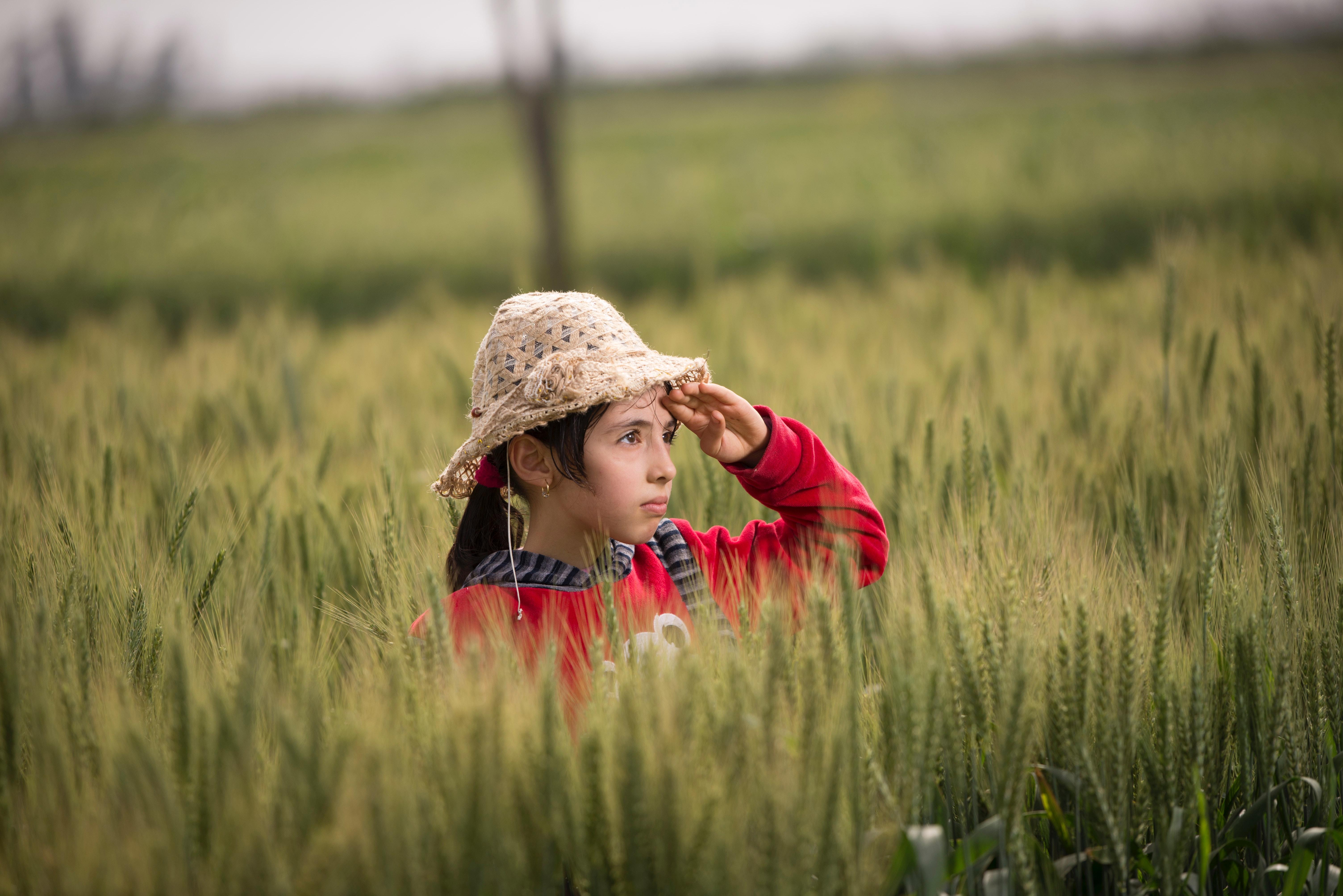 Girl in red hoodie wearing beige sunhat photo