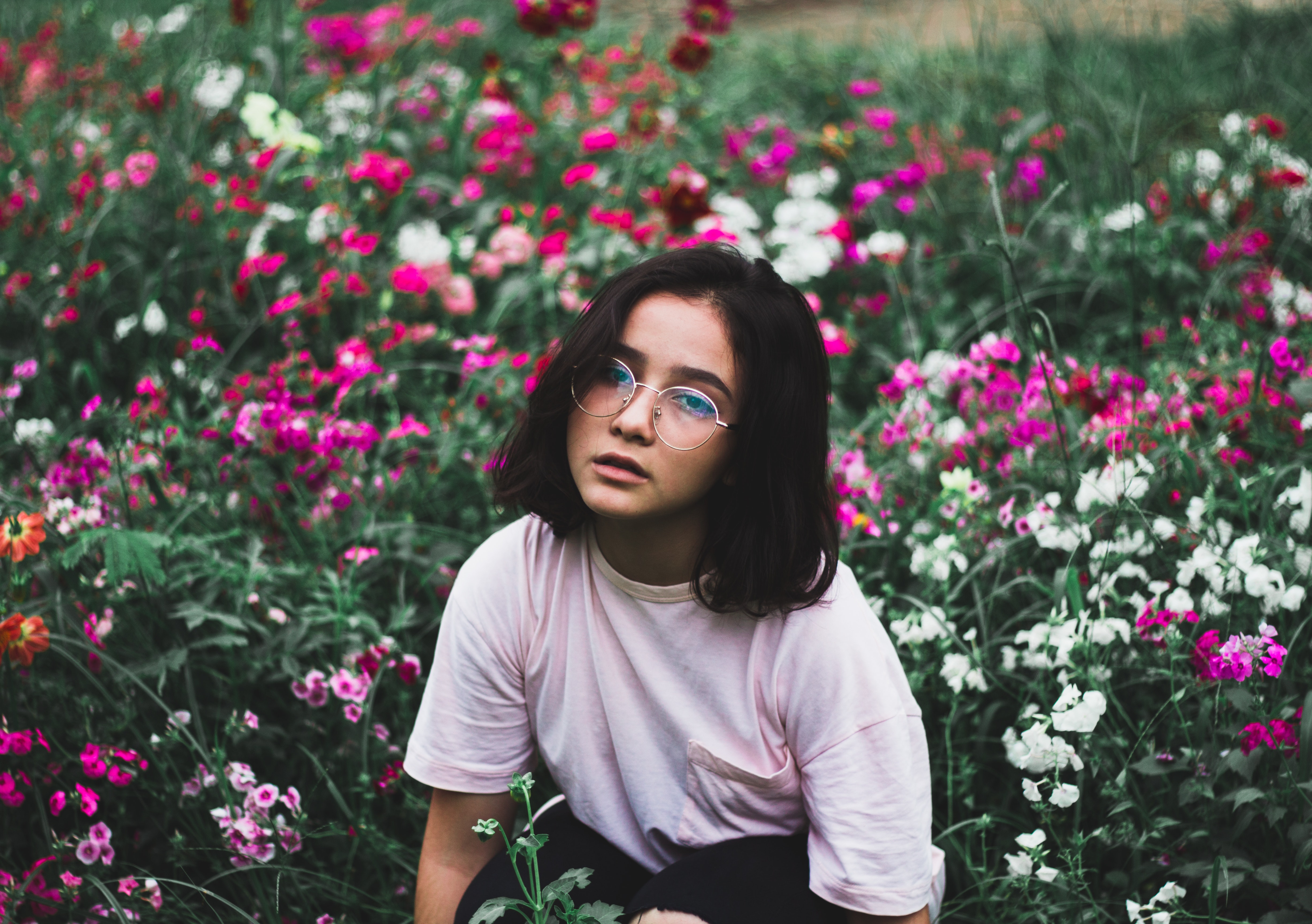 Girl in white t-shirt surrounded by flowers photo