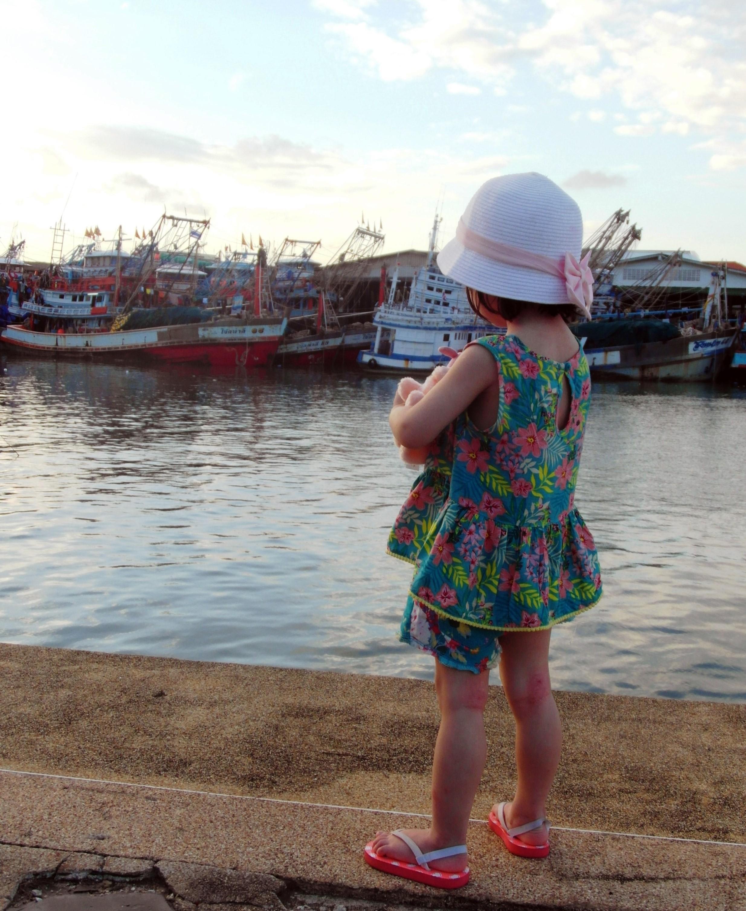 Girl looking at fishing boats photo