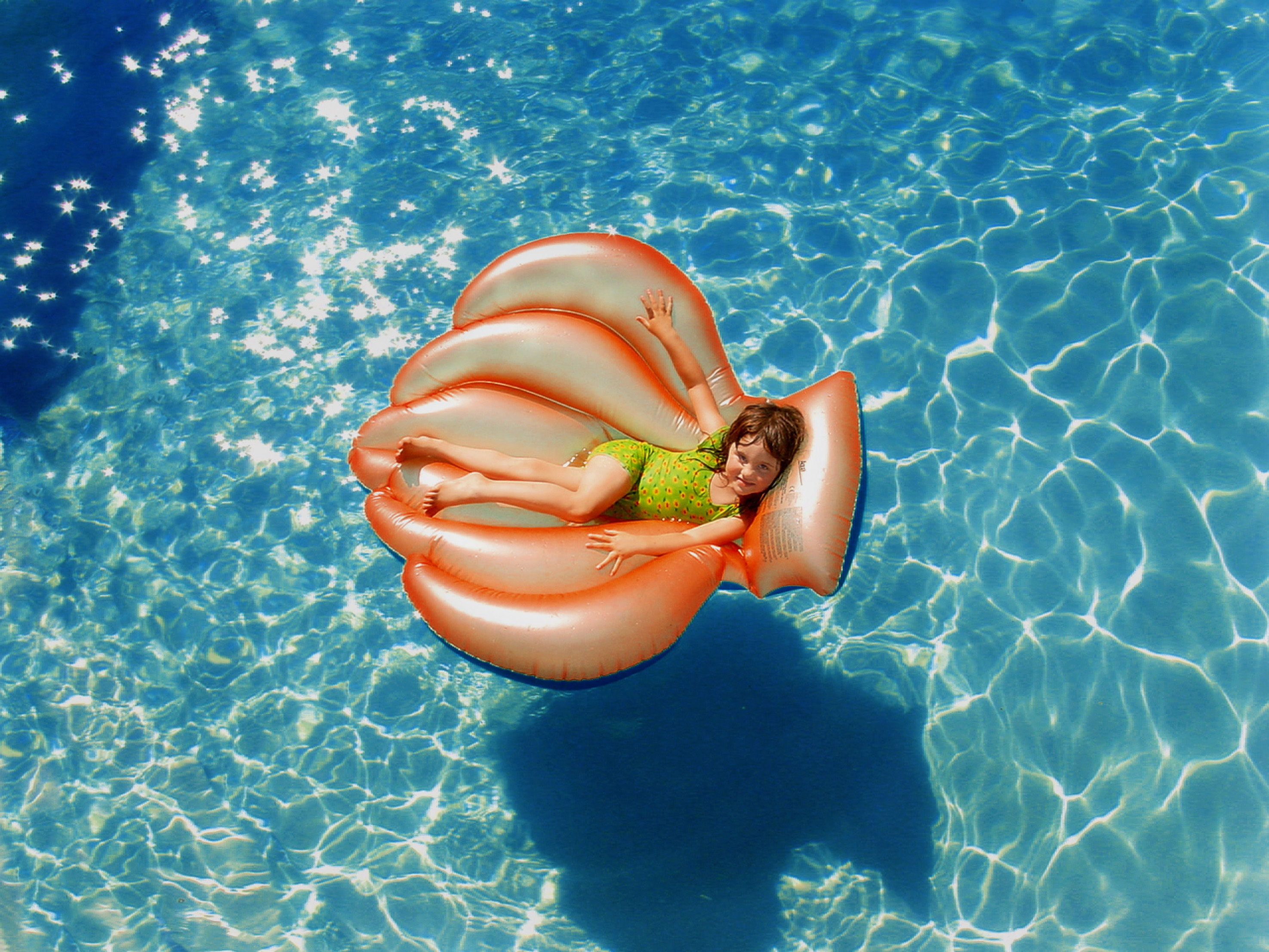 Girl wearing green wet suit riding inflatable orange life buoy on top of body of water photo