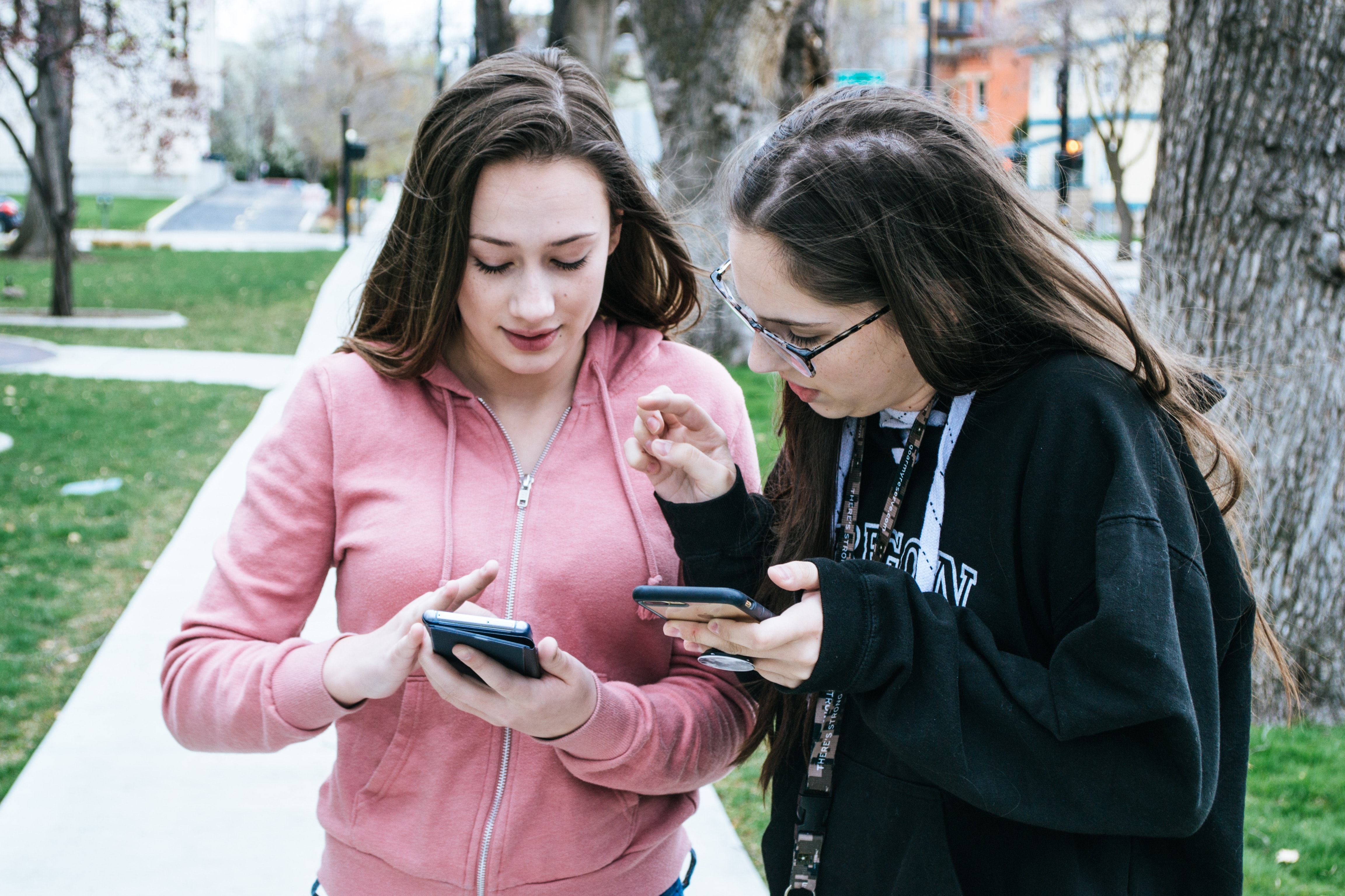 Girls show mobile photos to each other at the park