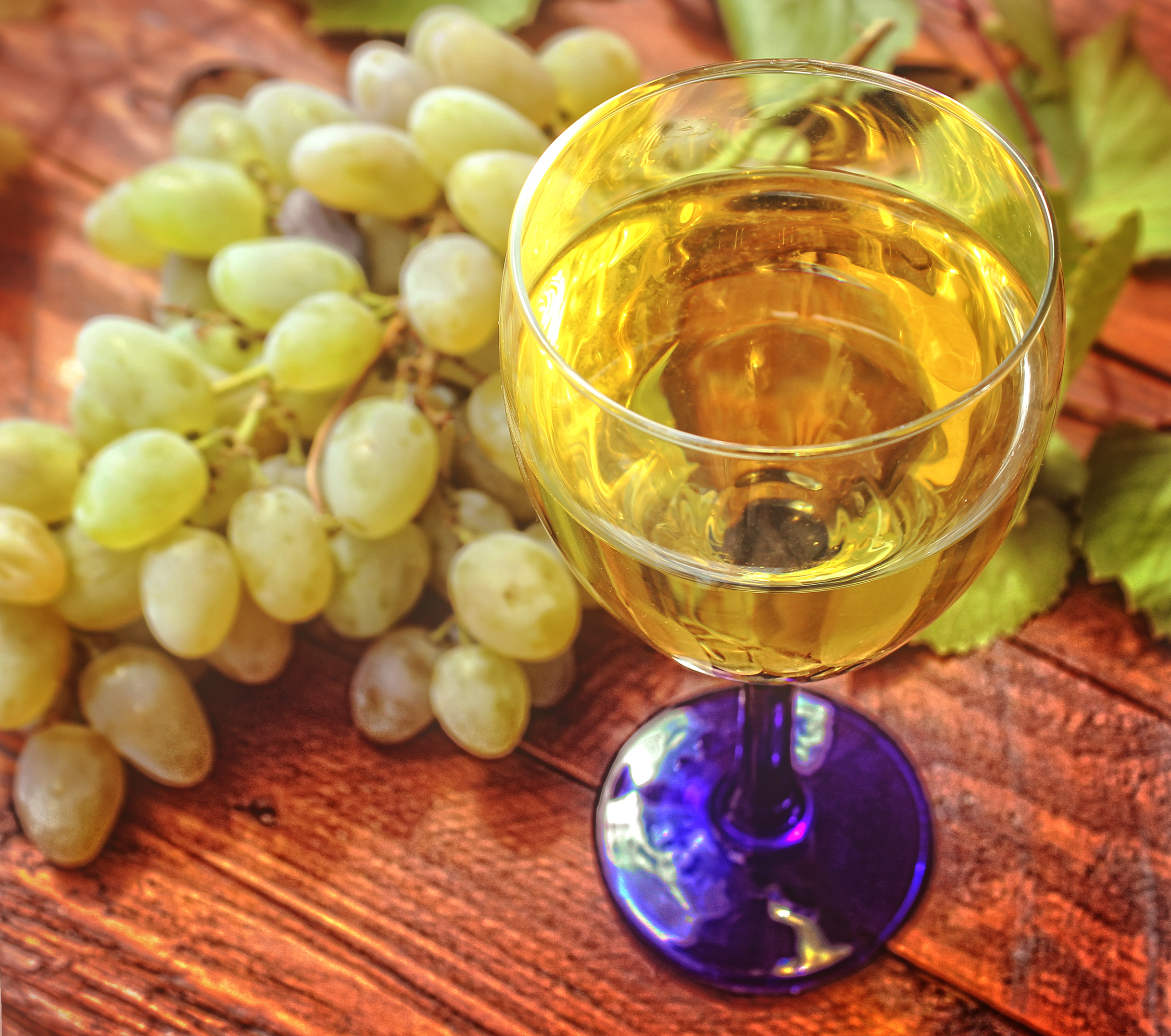 Glass of white wine and a bunch of grapes in the background photo