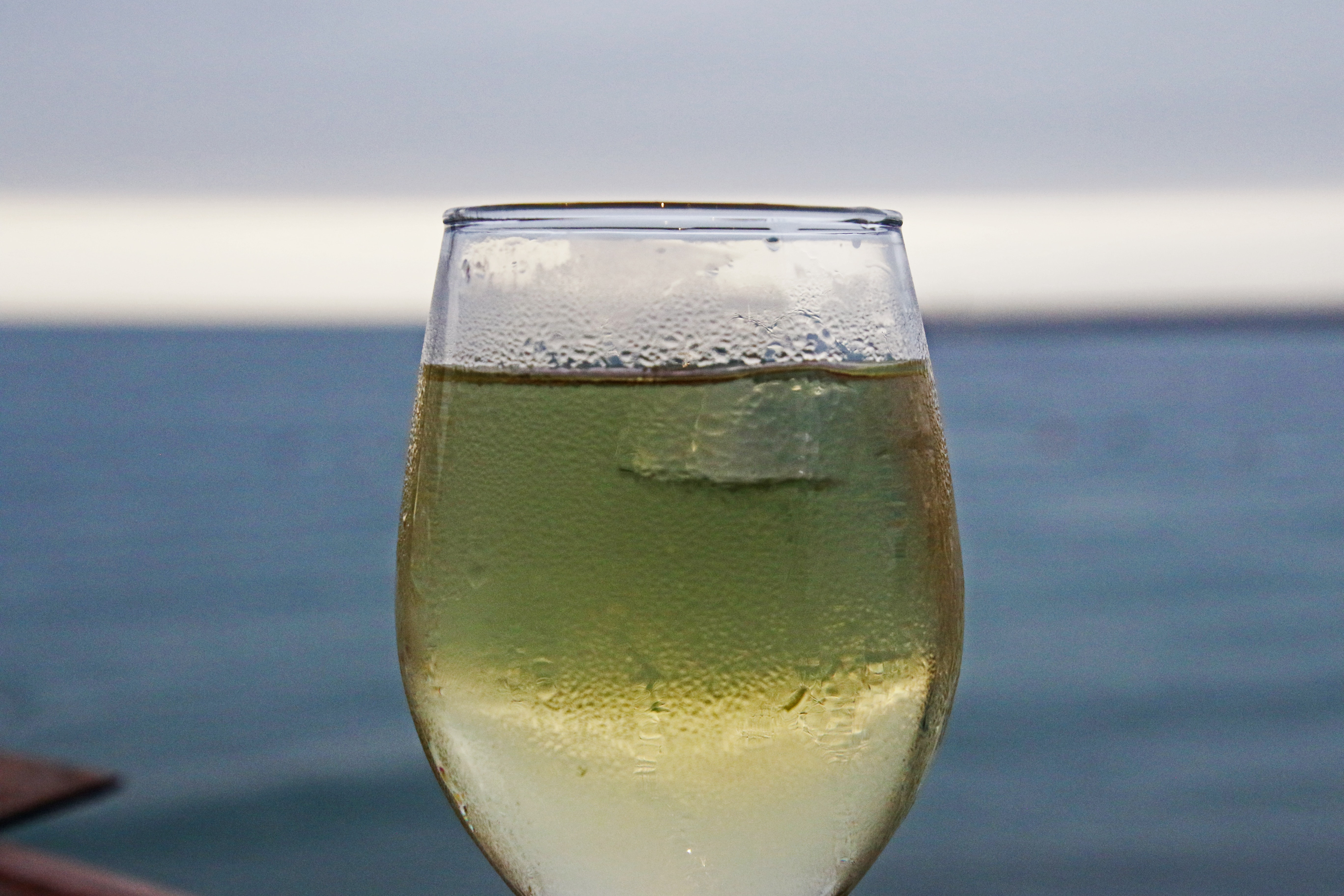 Glass of white wine on the beach photo