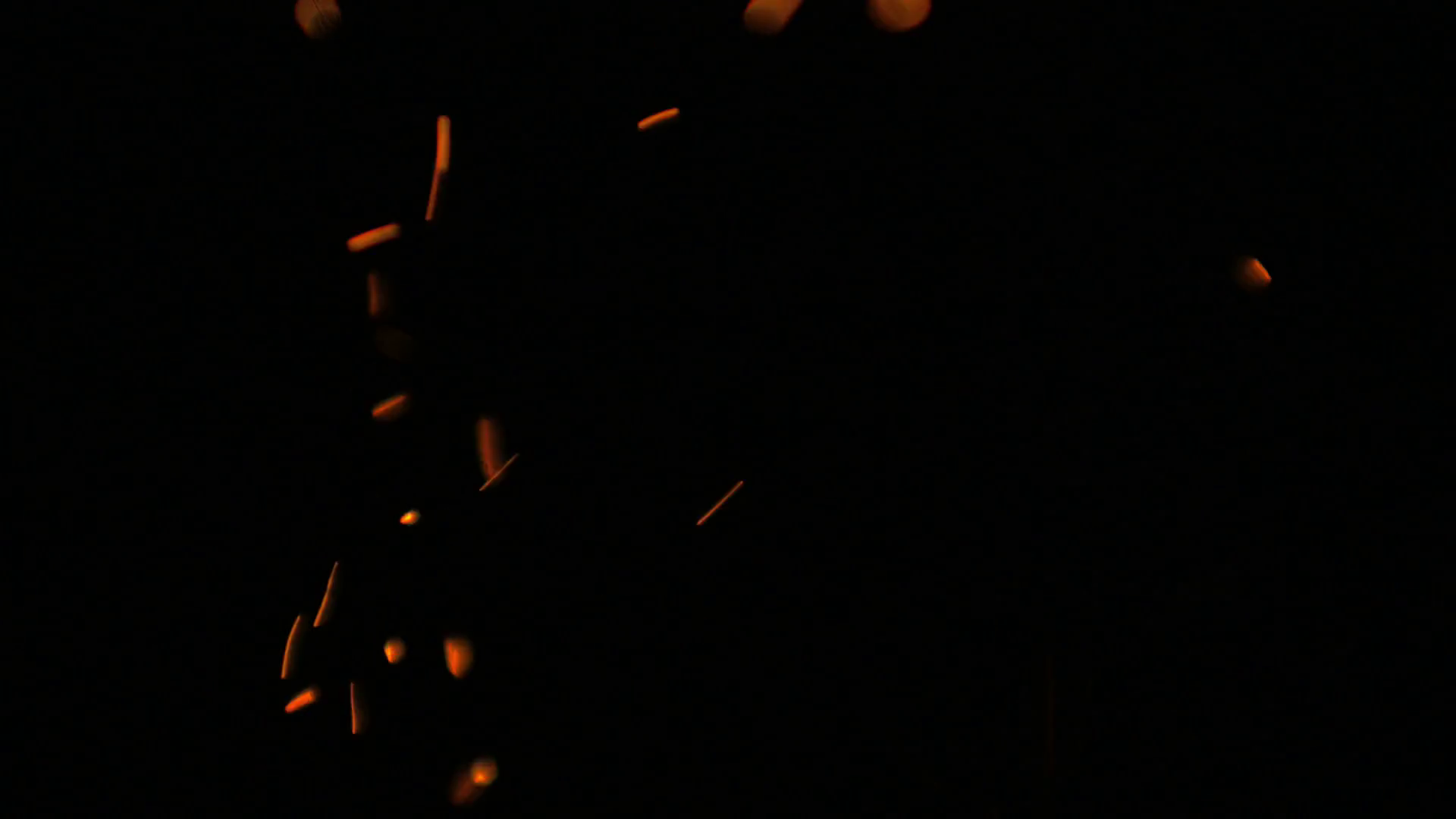 Static close up shallow depth of field shot of glowing fire spark ...