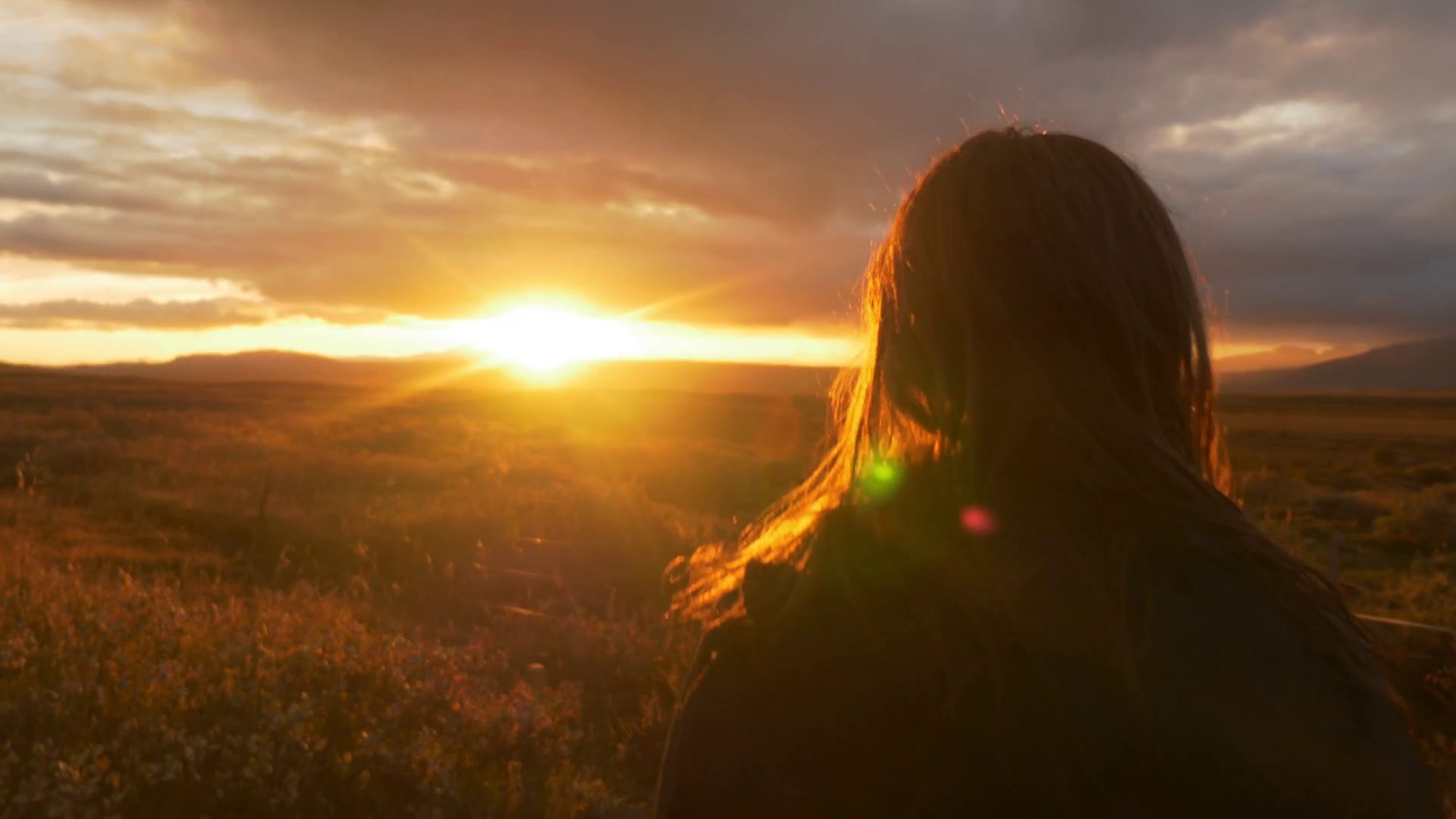 Iceland sunset at golden hour - girl looking into field Stock Video ...