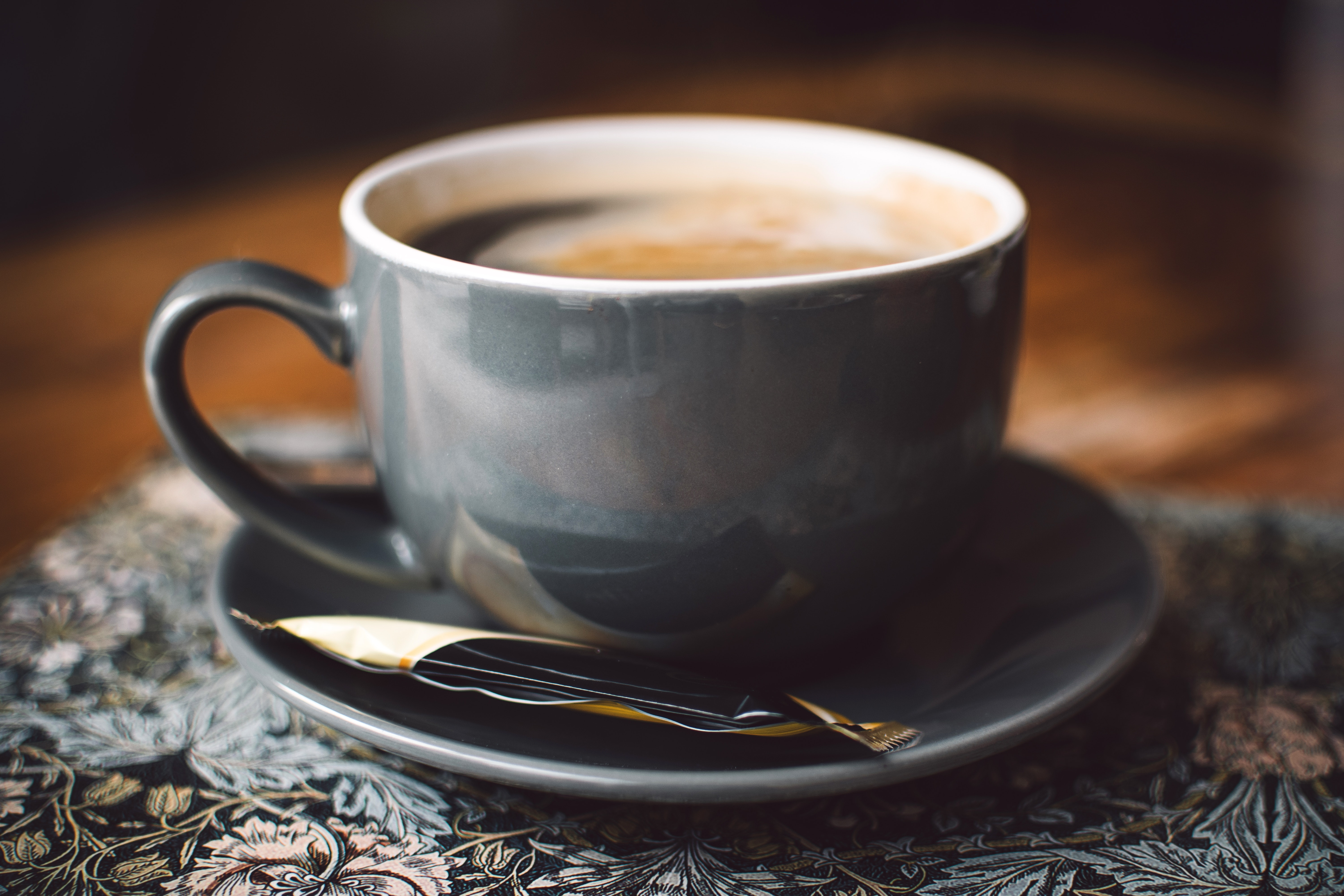 Gray ceramic cup of coffee on round gray saucer photo