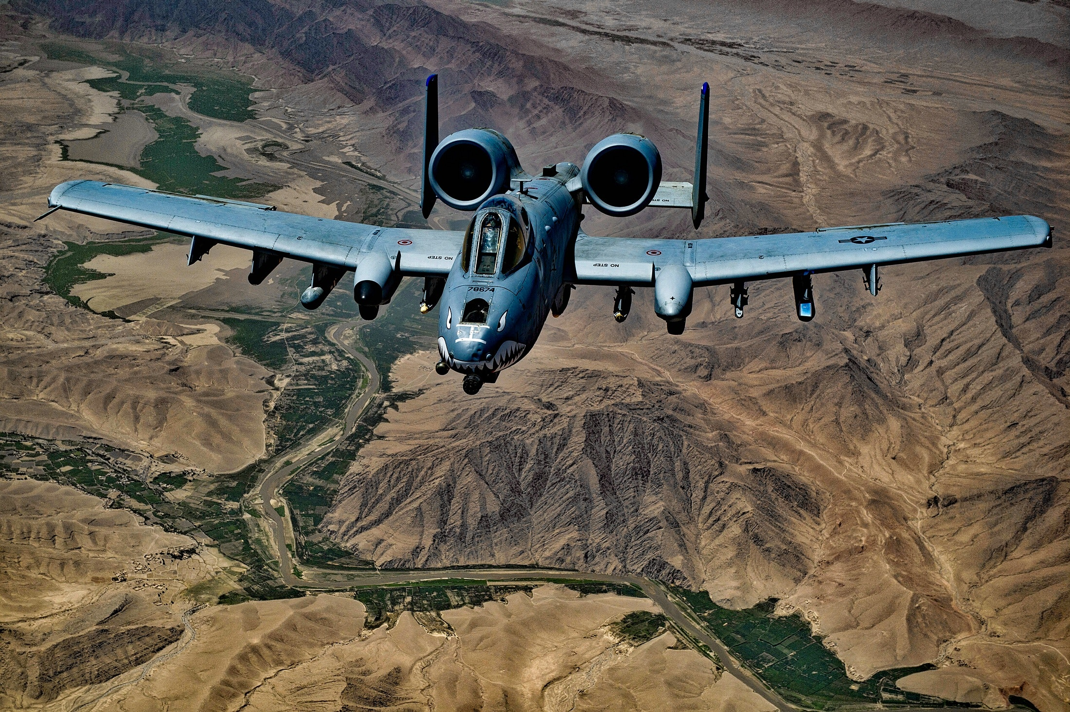 Gray jet fighter flying above brown mountain photo