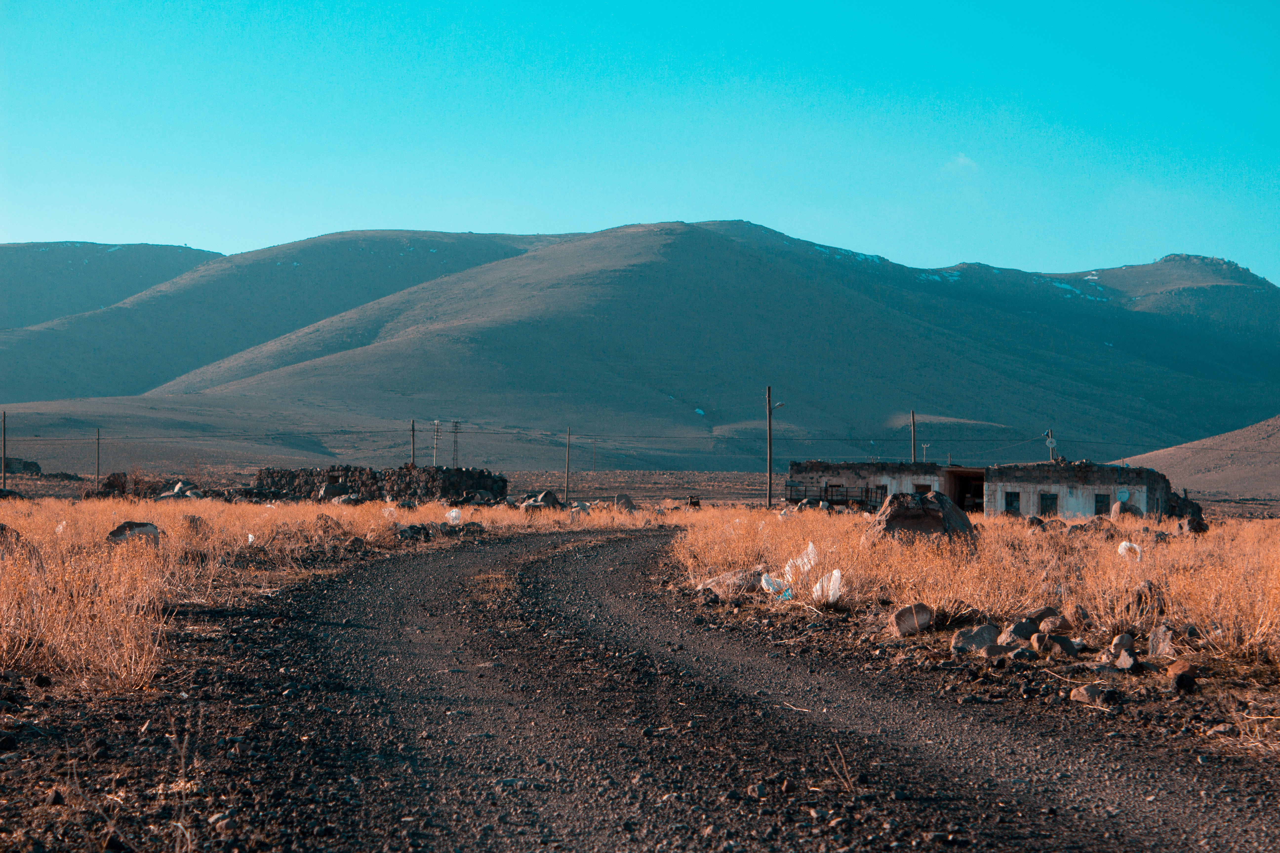 Gray road in between brown grass field with mountains background photo