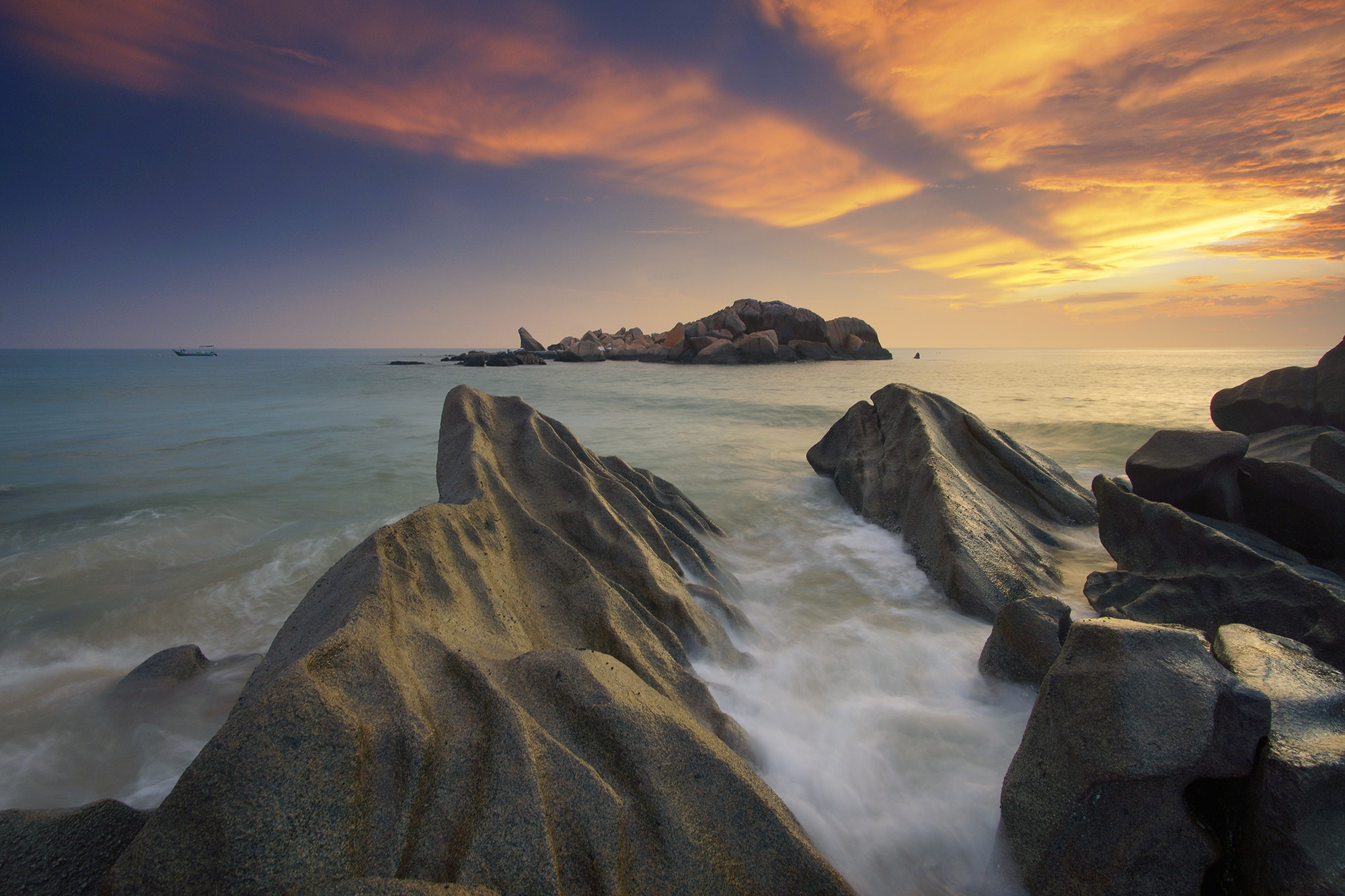 Gray rock formation near body of water during sunset photo