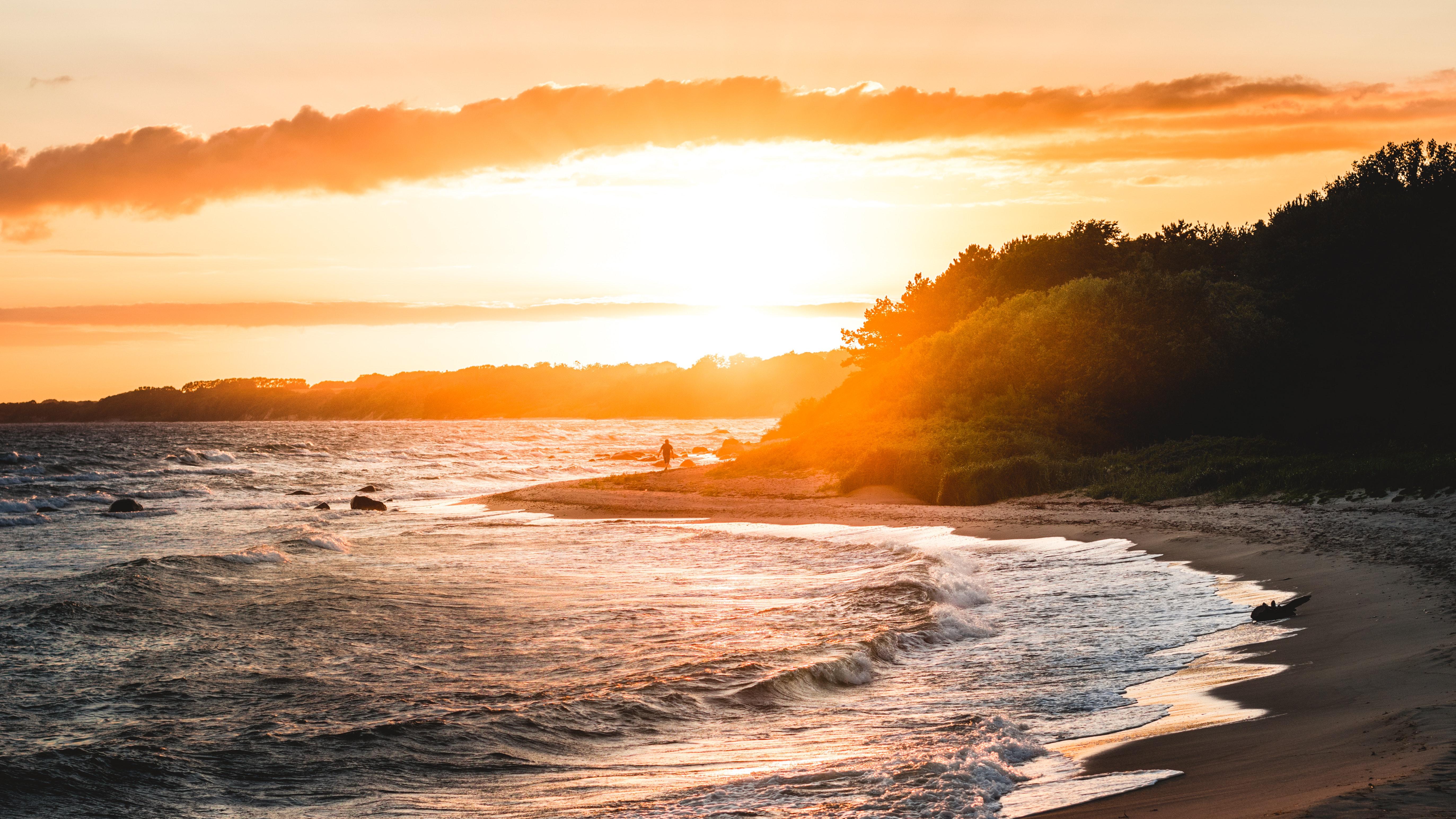 Gray sand beach during sunset photo