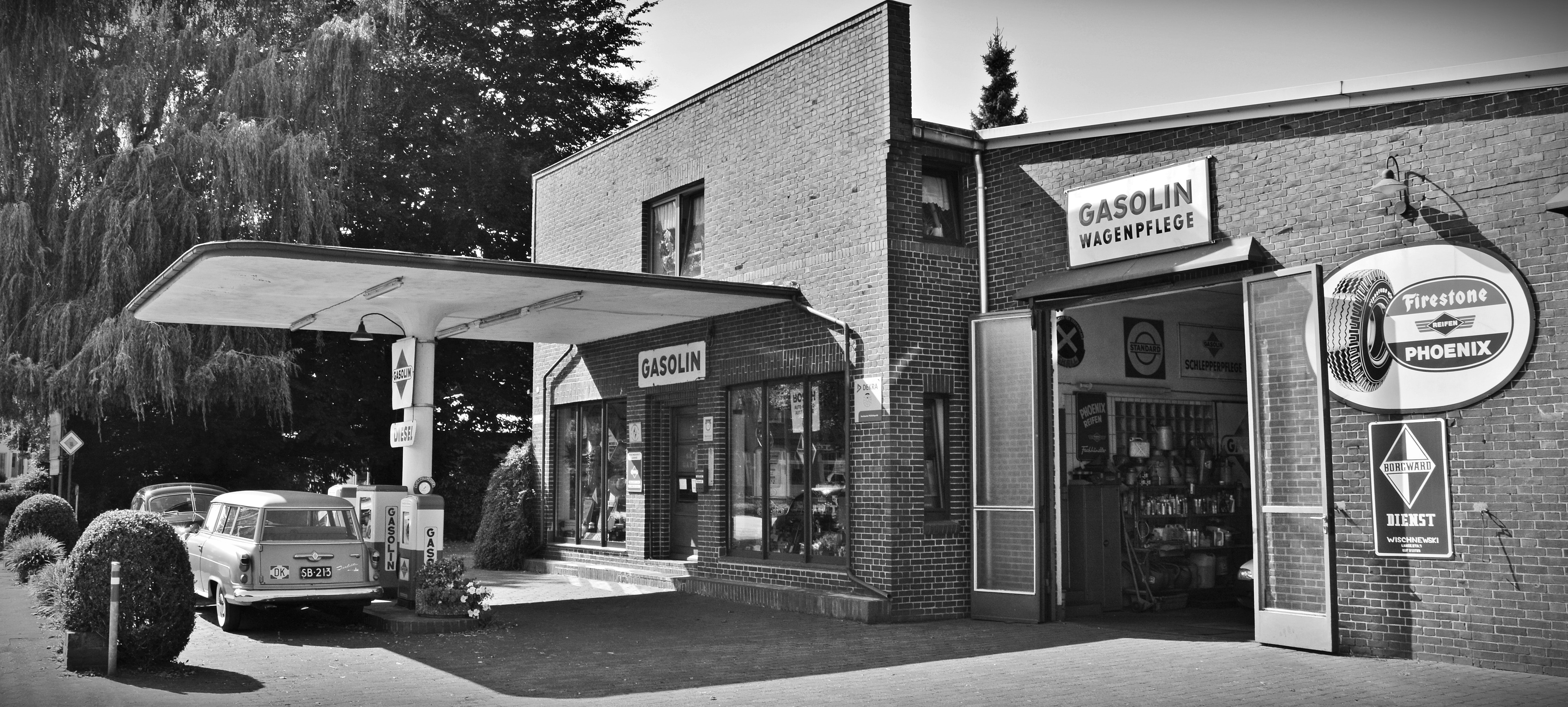 Gray scale photo of a sedan parked infront of store