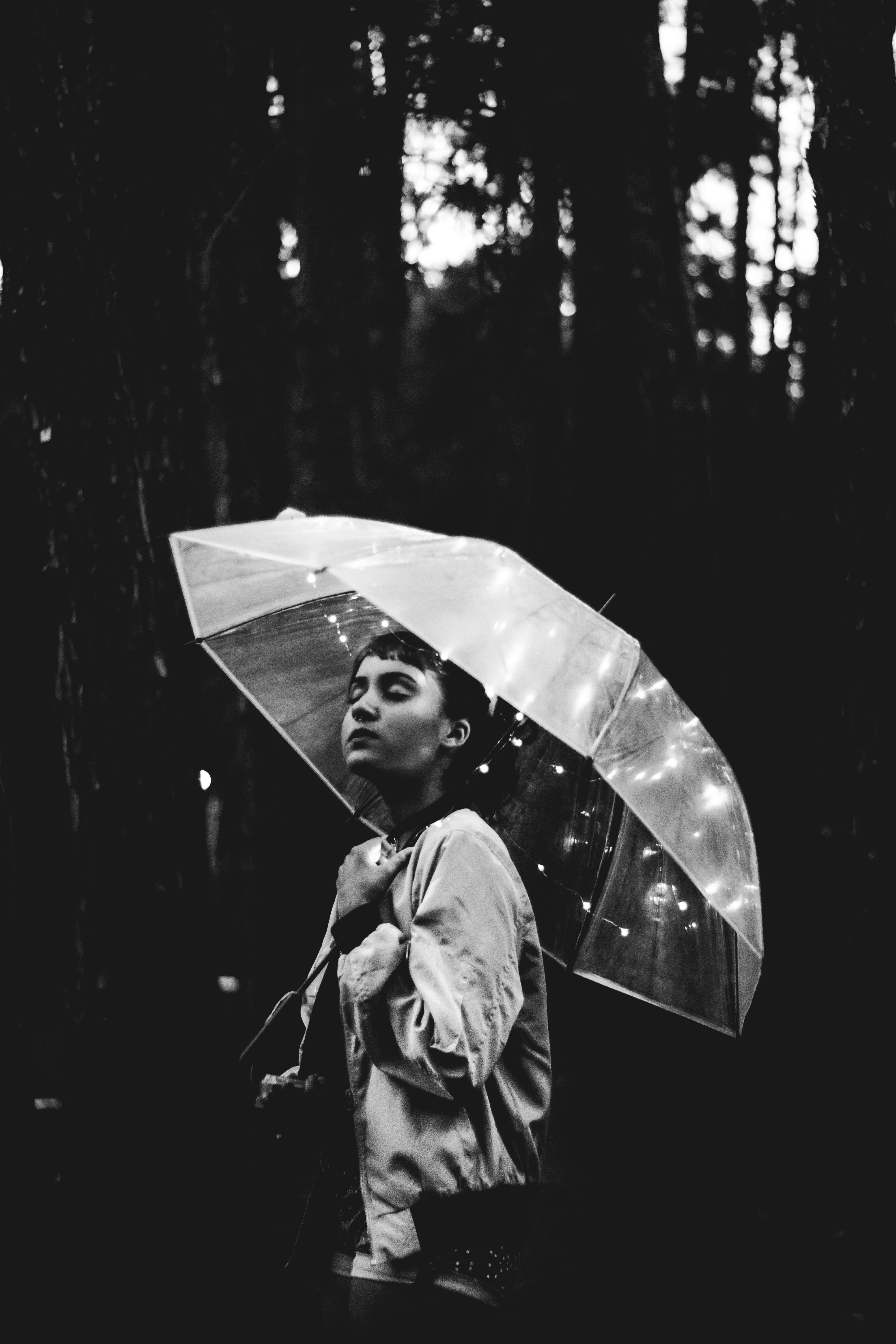 Grayscale image of woman walking through the rain while holding umbrella photo