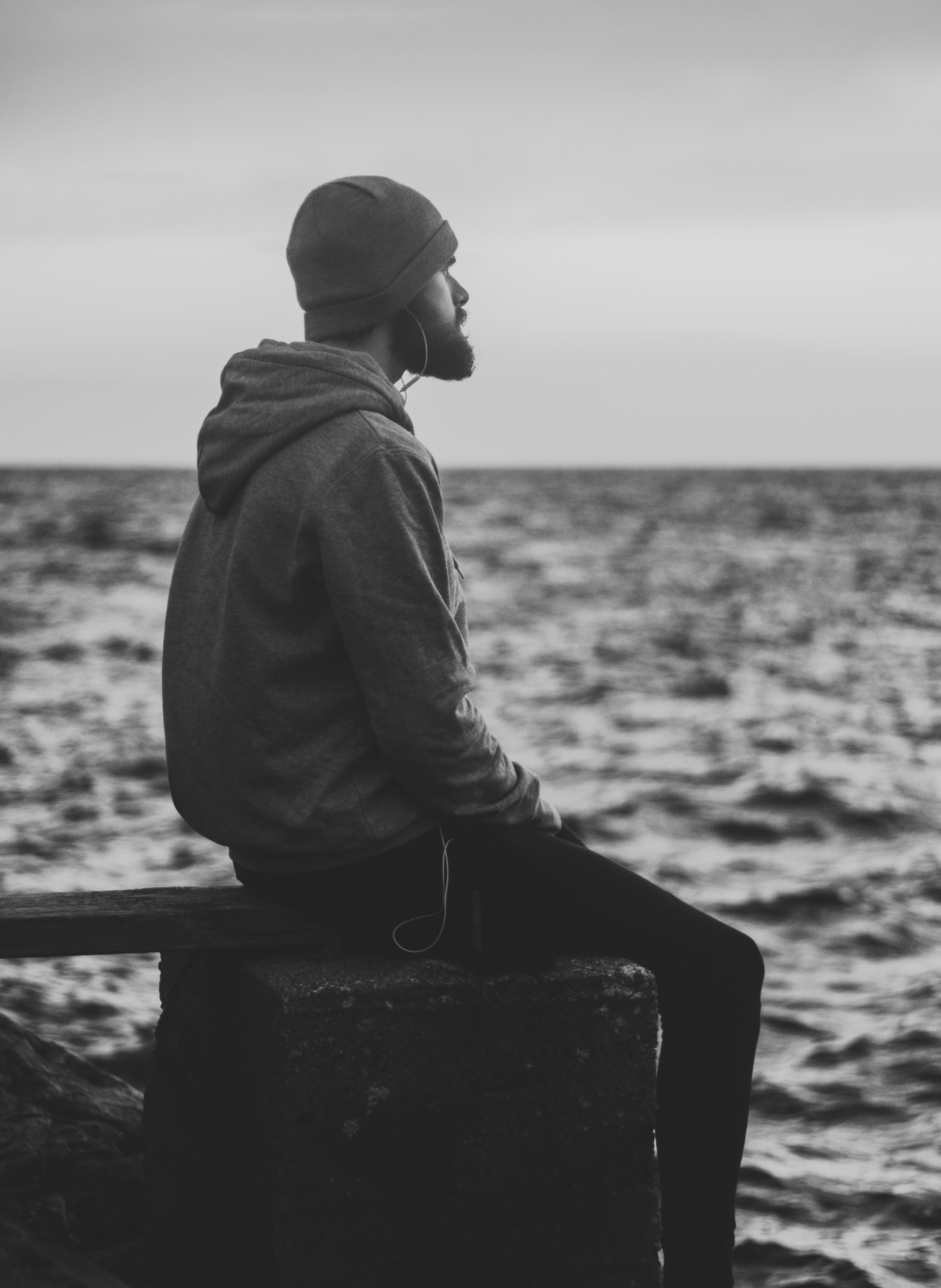 Grayscale Photo of Man in Hoodie and Kit Cap Sitting Near Bodies of Water, Sea, Outdoors, Seashore, Water, HQ Photo