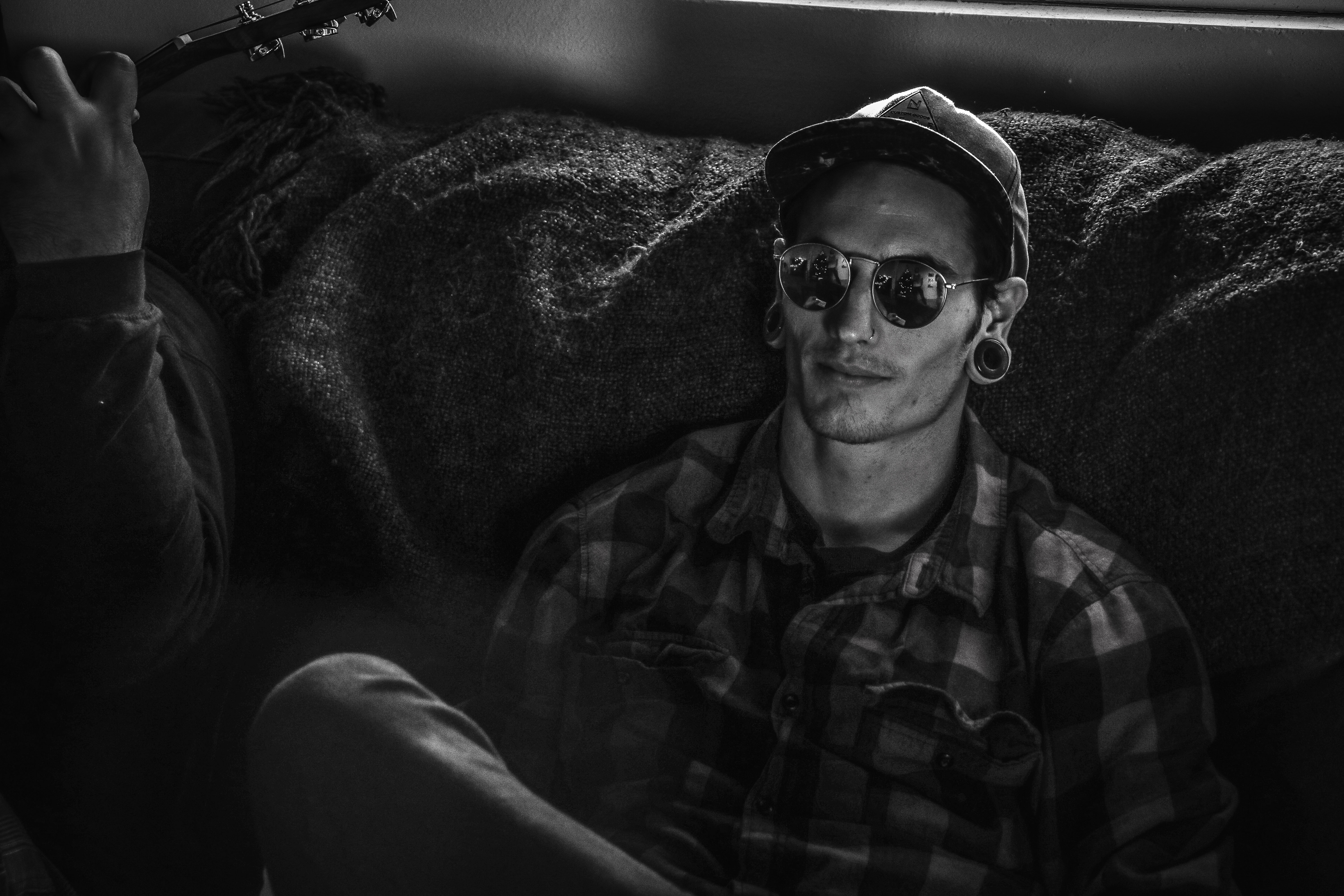 Grayscale Photo of Man Wearing Snapback Cap and Plaid Dress Shirt Sitting on Couch, Adult, Black-and-white, Couch, Earrings, HQ Photo