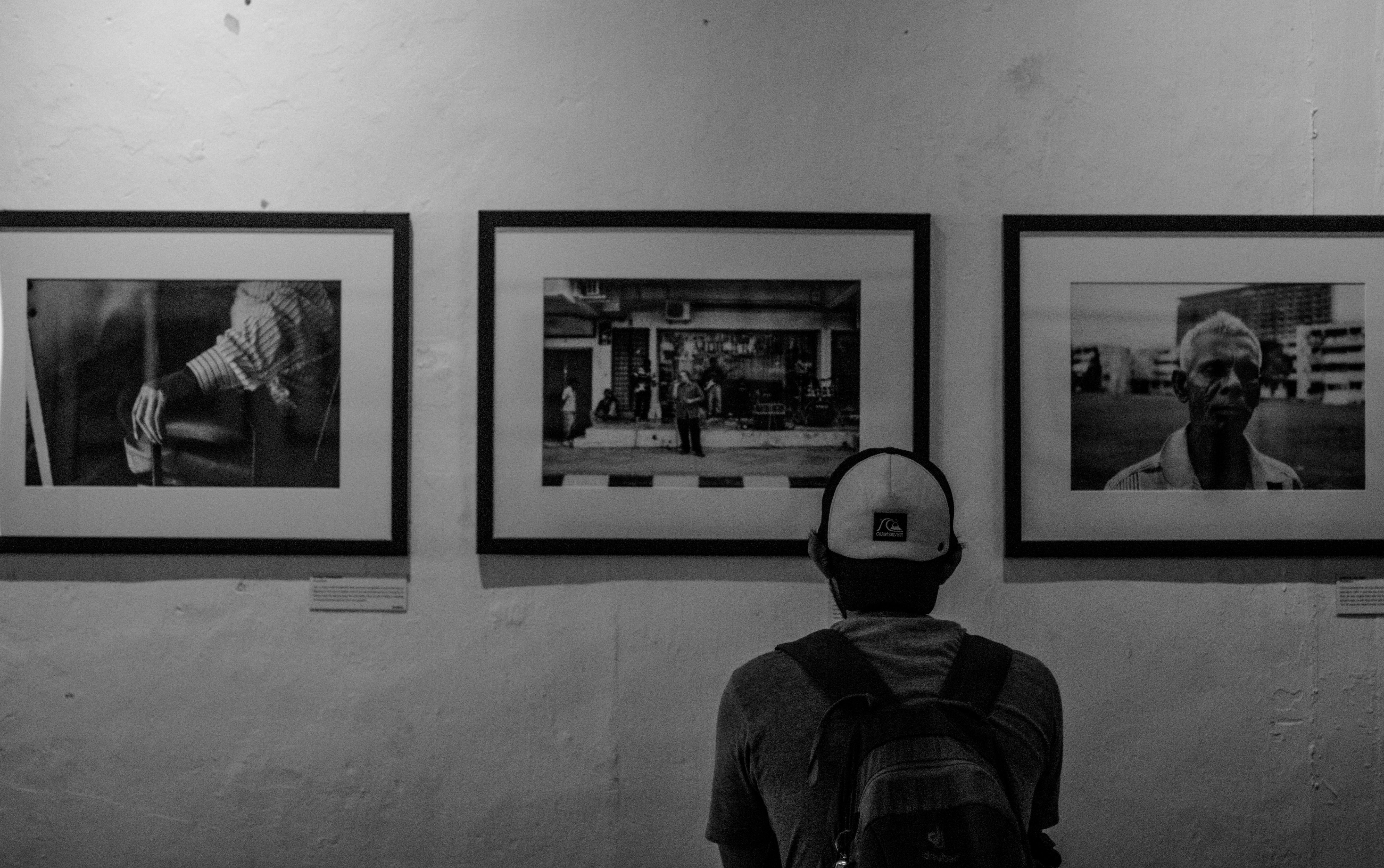 Grayscale photo of man wearing white cap in front of three paintings painting museum