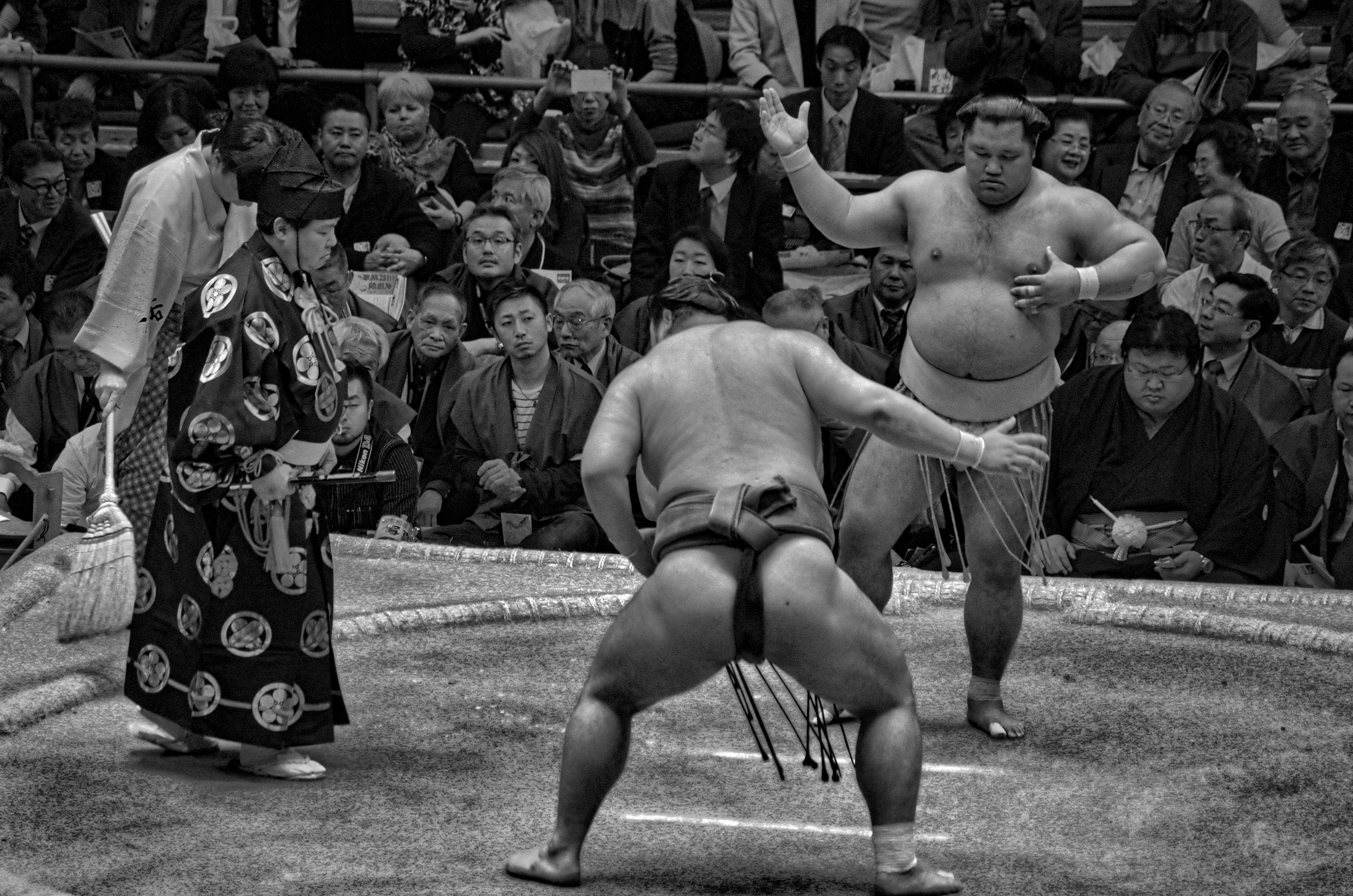 Grayscale photo of sumo wrestling surrounded with people