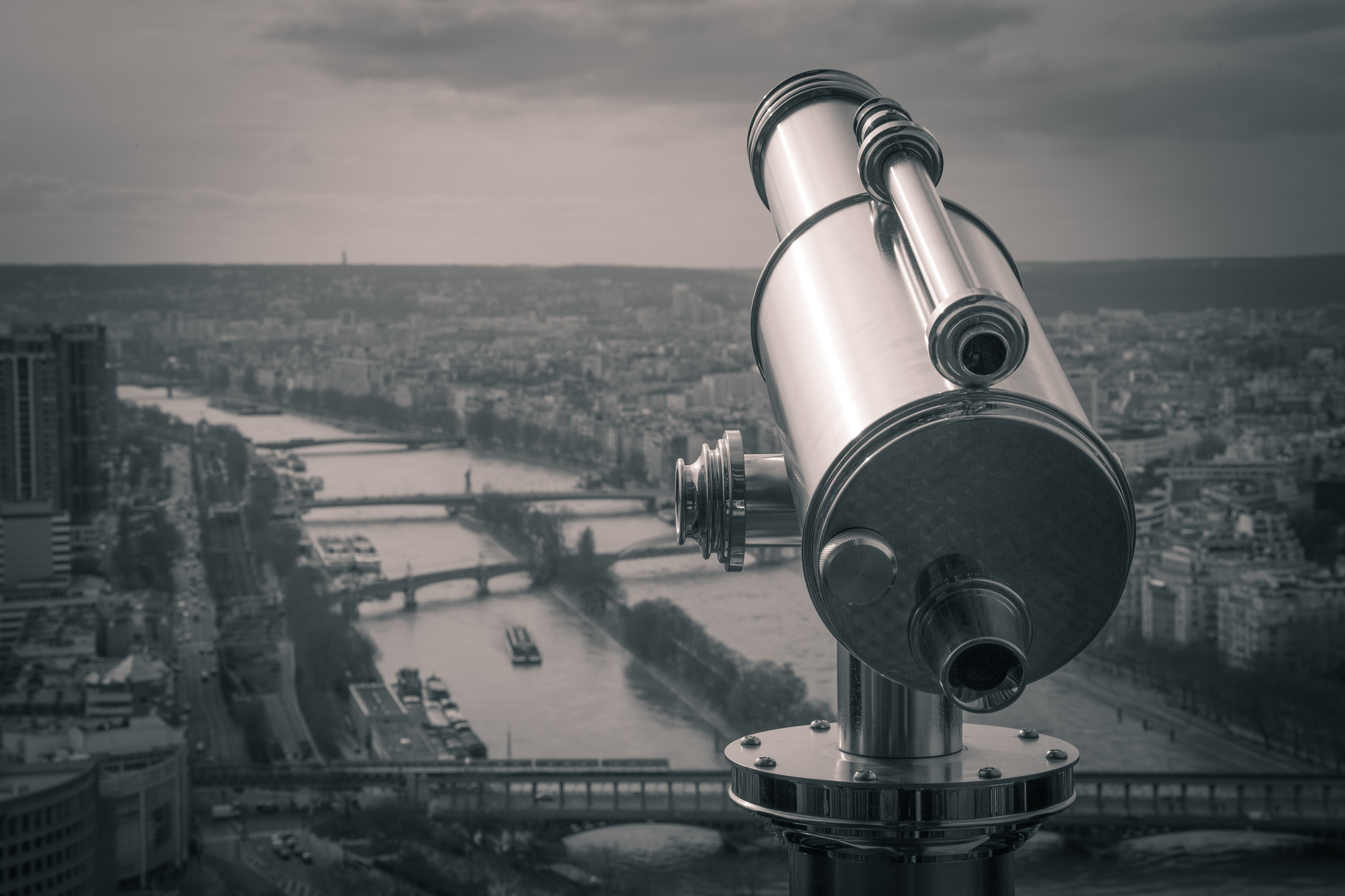 Grayscale photography of observation telescope overlooking city riverbank