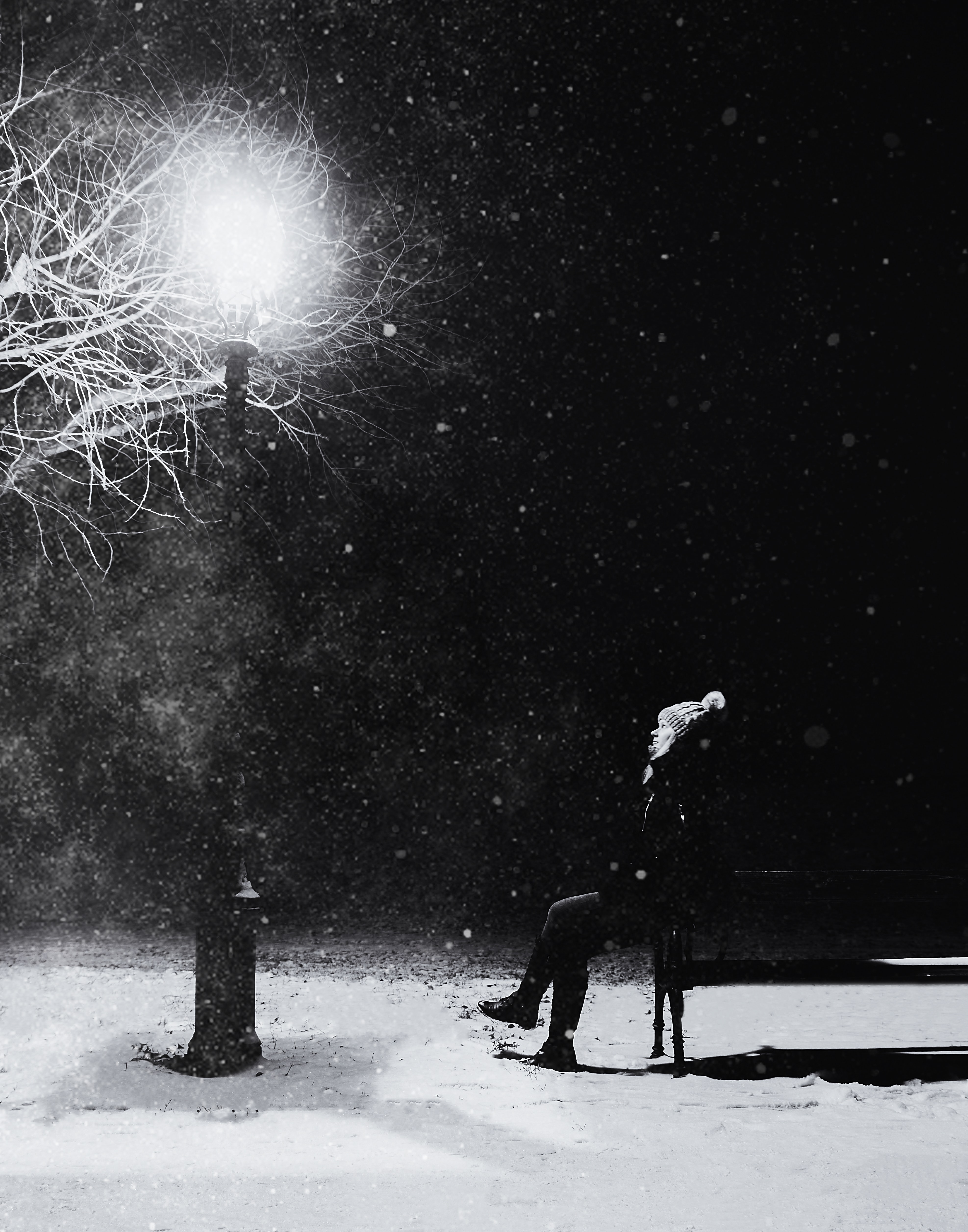 Grayscale Photography of Person With Knit Pompom Cap Sits in Front Turned on Light Post at Night, Adult, Snow, Winter, Weather, HQ Photo