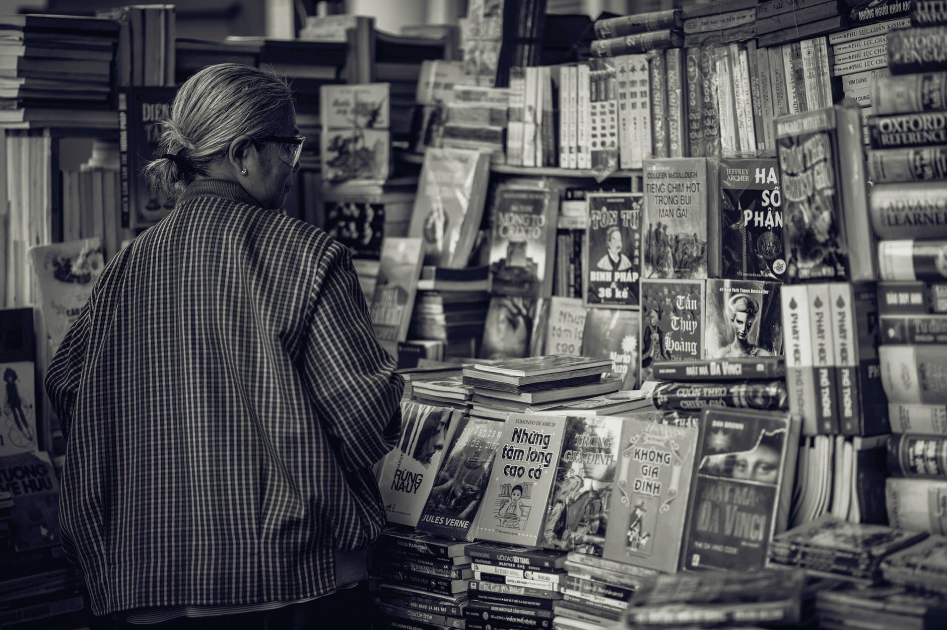 Grayscale photography of woman looking at the books