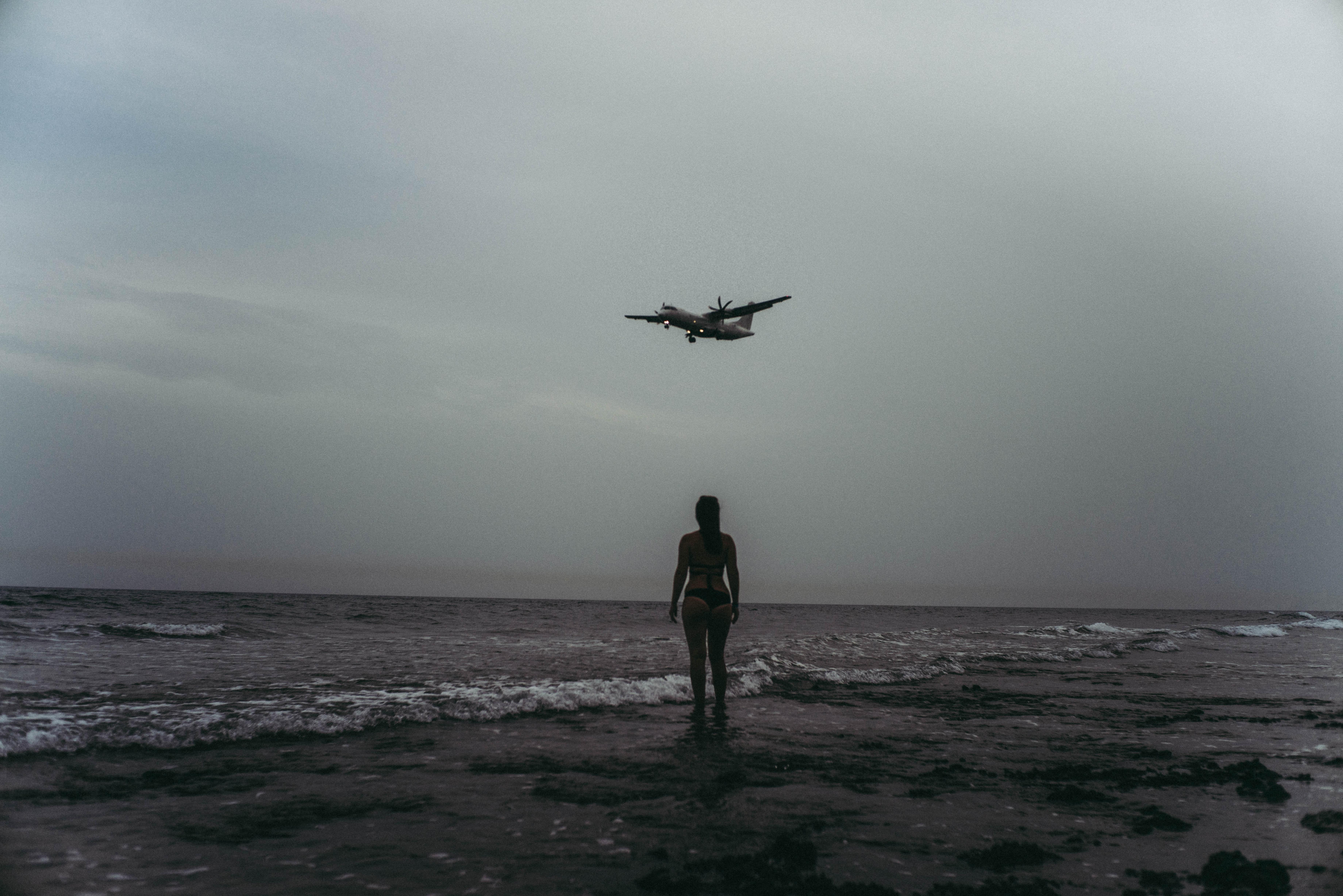 Grayscale Photography Of Woman On Seashore, Aeroplane, Monochrome, Water, Sky, HQ Photo