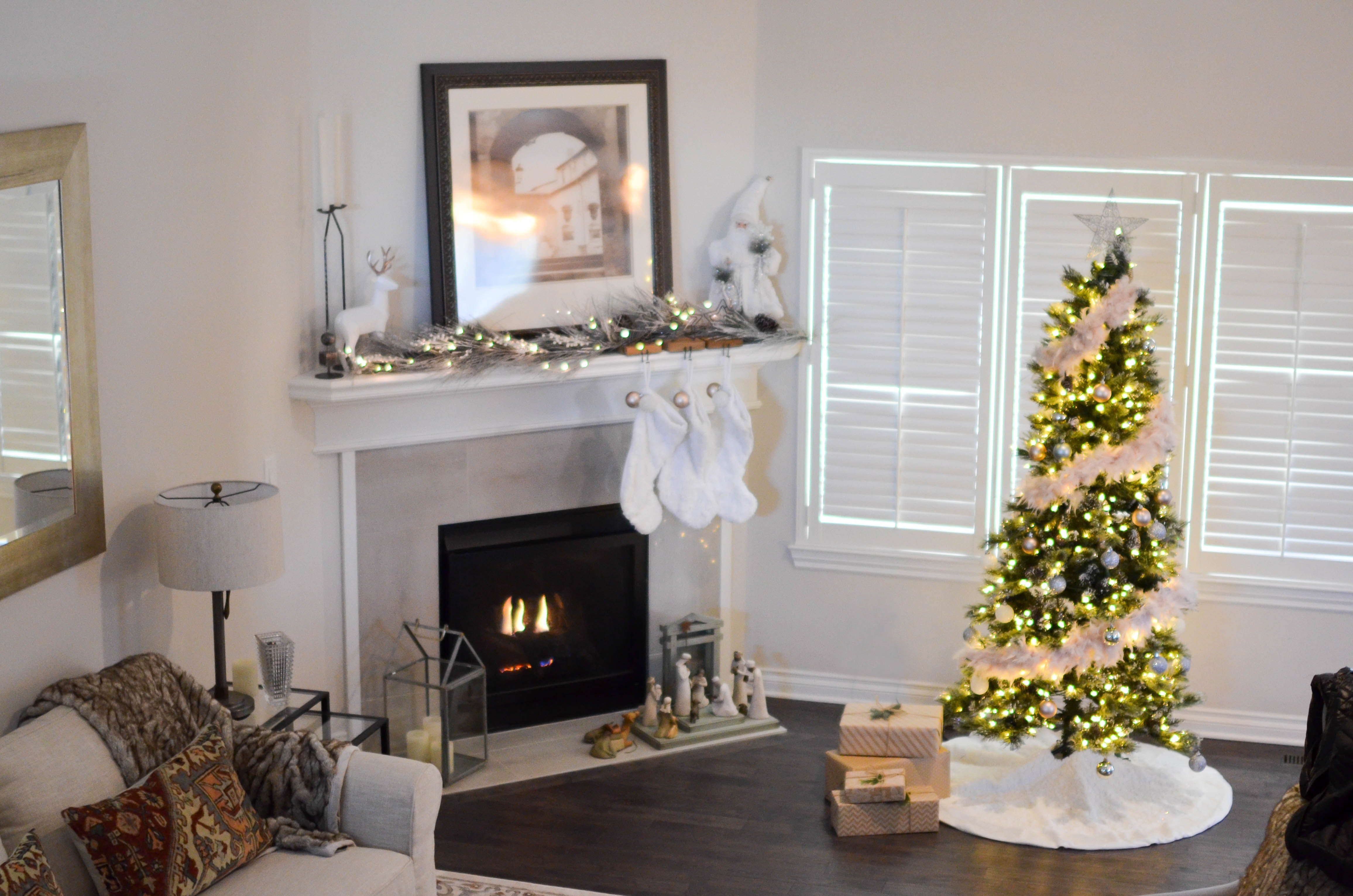 Green and white pre-lit pine tree near fireplace inside well lit room photo