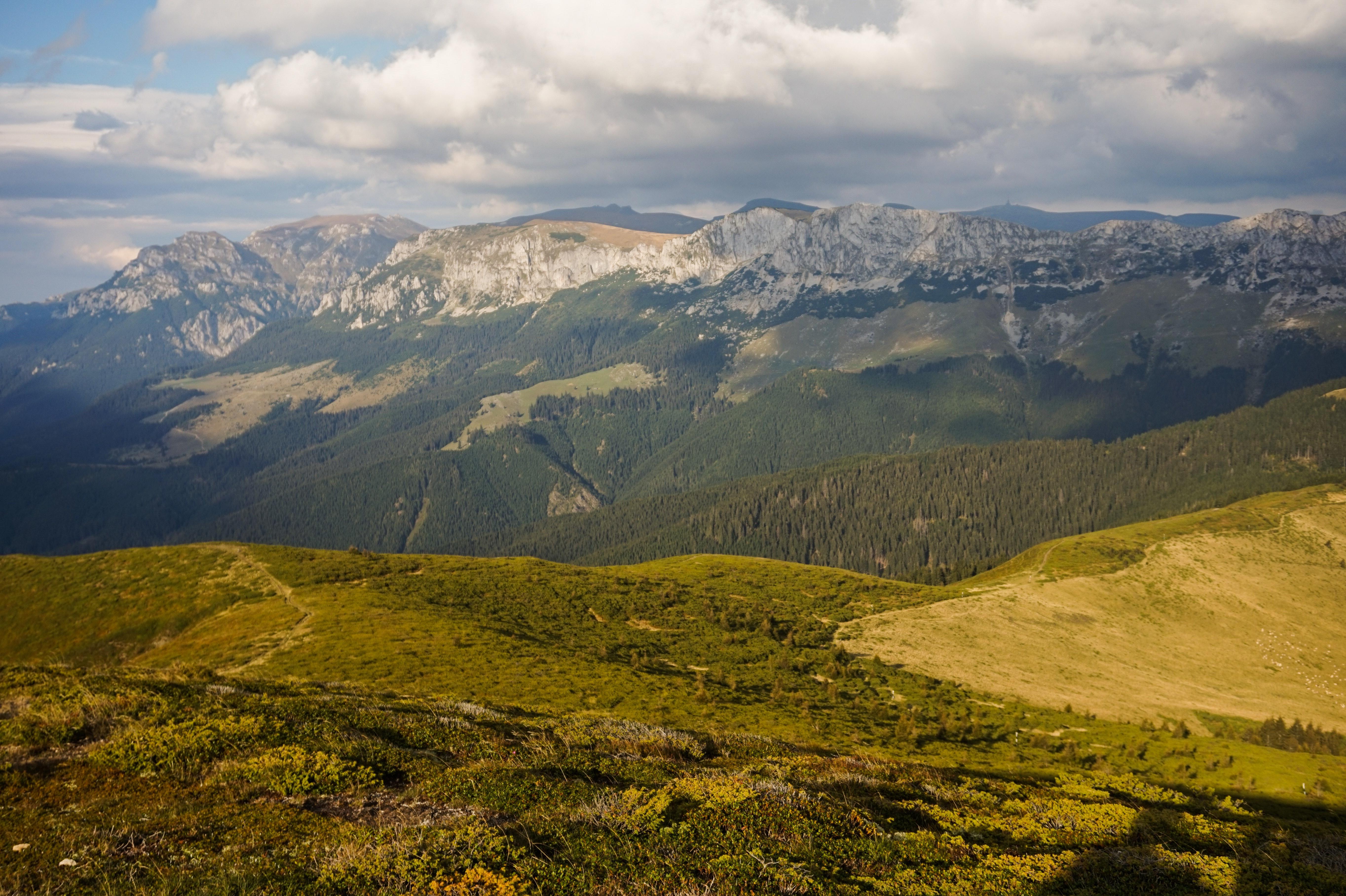 Green mountain range under cloudy skies photo